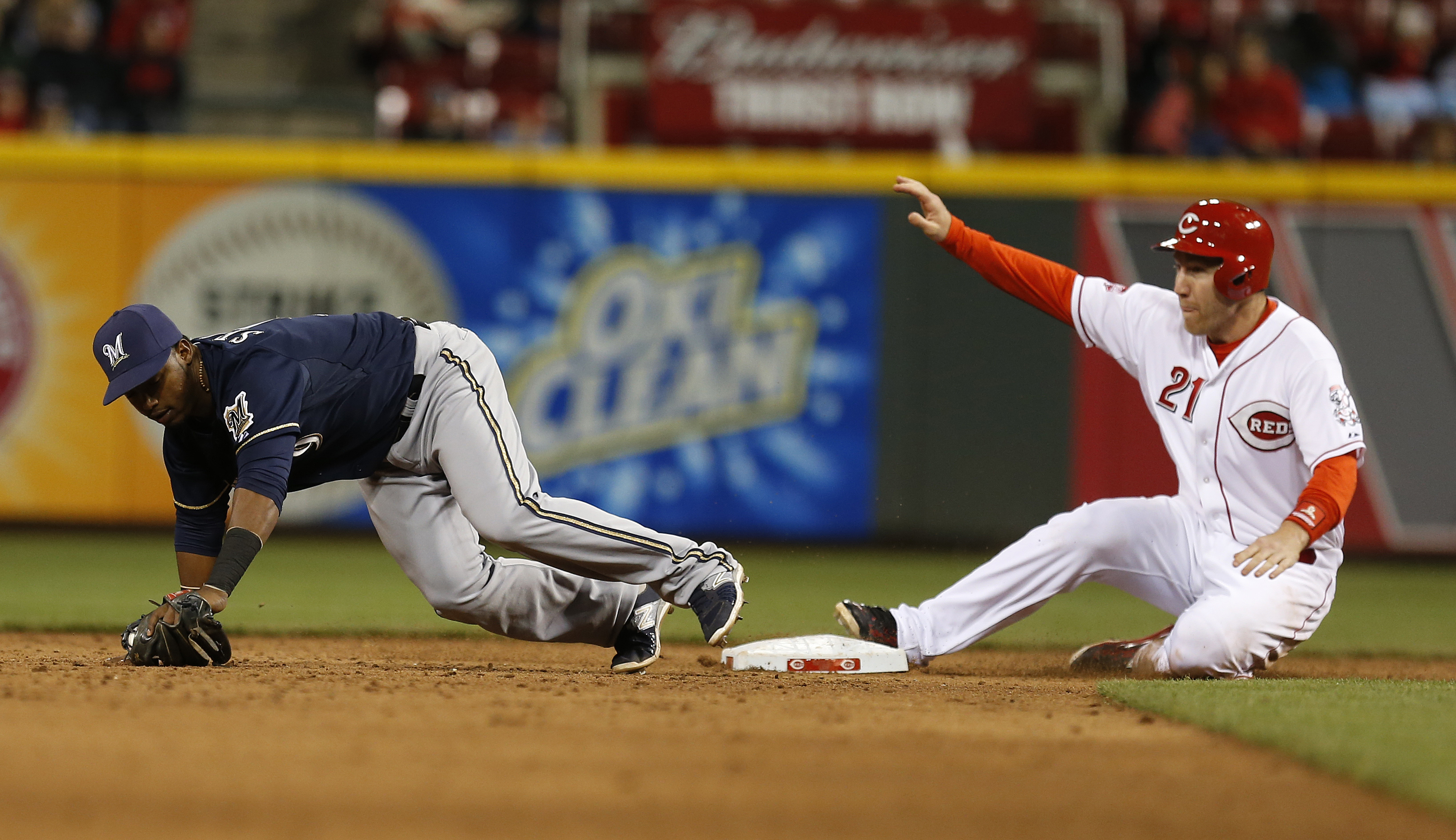 Cincinnati Reds' Todd Frazier (21) is safe at second base with a steal as Milwaukee Brewers' shortstop Jean Segura takes the wide throw during the sixth inning of a baseball game Monday, April 27, 2015, in Cincinnati. (AP Photo/Gary Landers)
