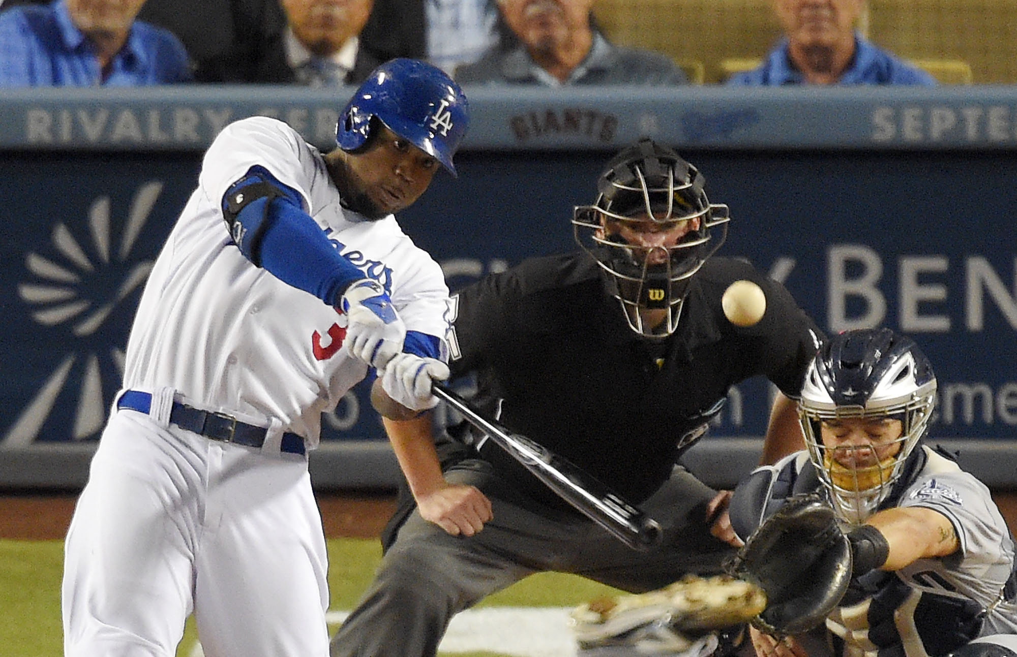 FILE - In this Wednesday, Sept. 10, 2014 file photo, Los Angeles Dodgers' Carl Crawford, left, hits an RBI double as San Diego Padres catcher Rene Rivera, right, looks on along with home plate umpire Tom Woodring during the third inning of a baseball game