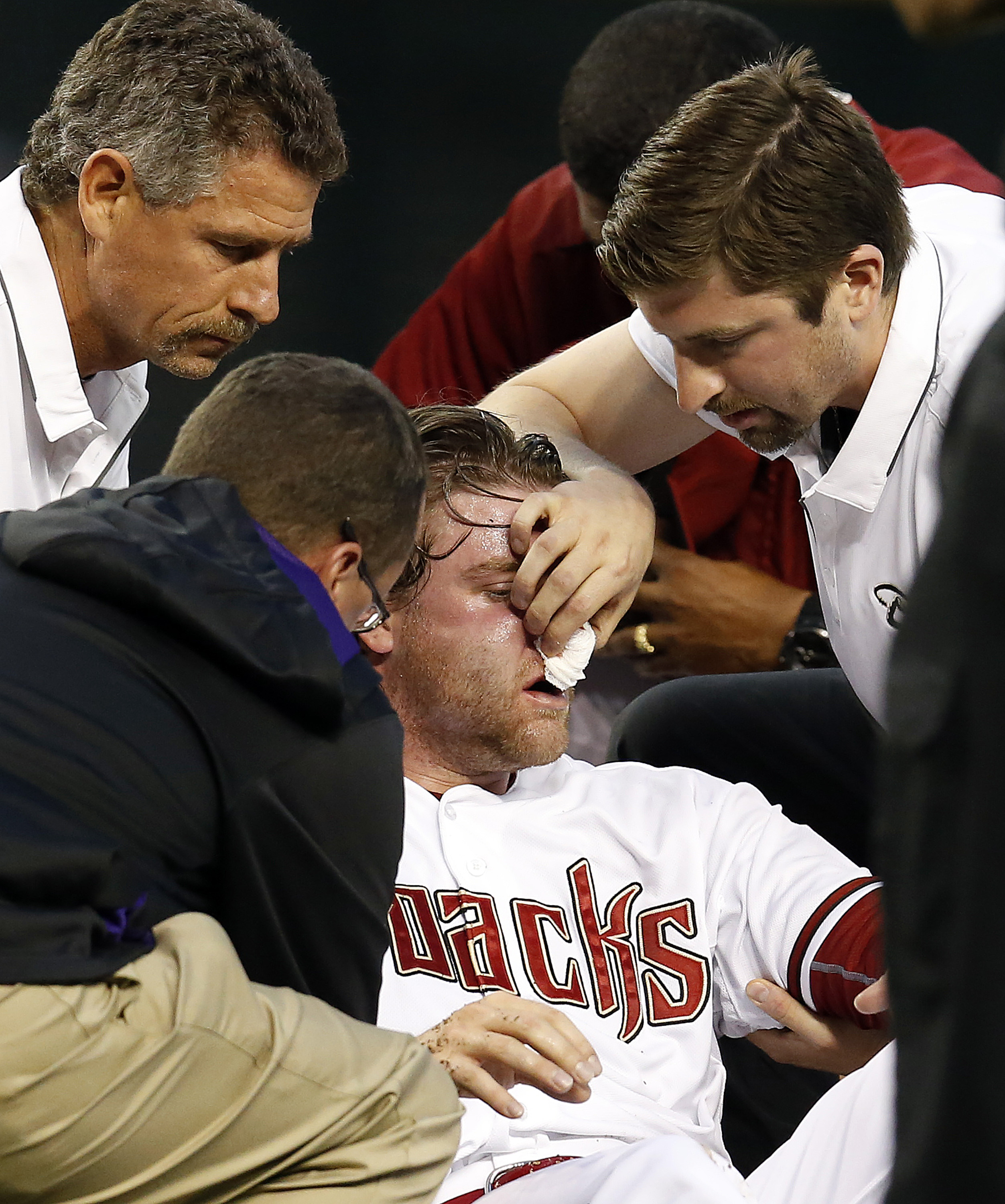 Trainers attend to Arizona Diamondbacks pitcher Archie Bradley (25) in the second inning after getting hit with a line drive during a baseball game against the Colorado Rockies, Tuesday, April 28, 2015, in Phoenix. (AP Photo/Rick Scuteri)