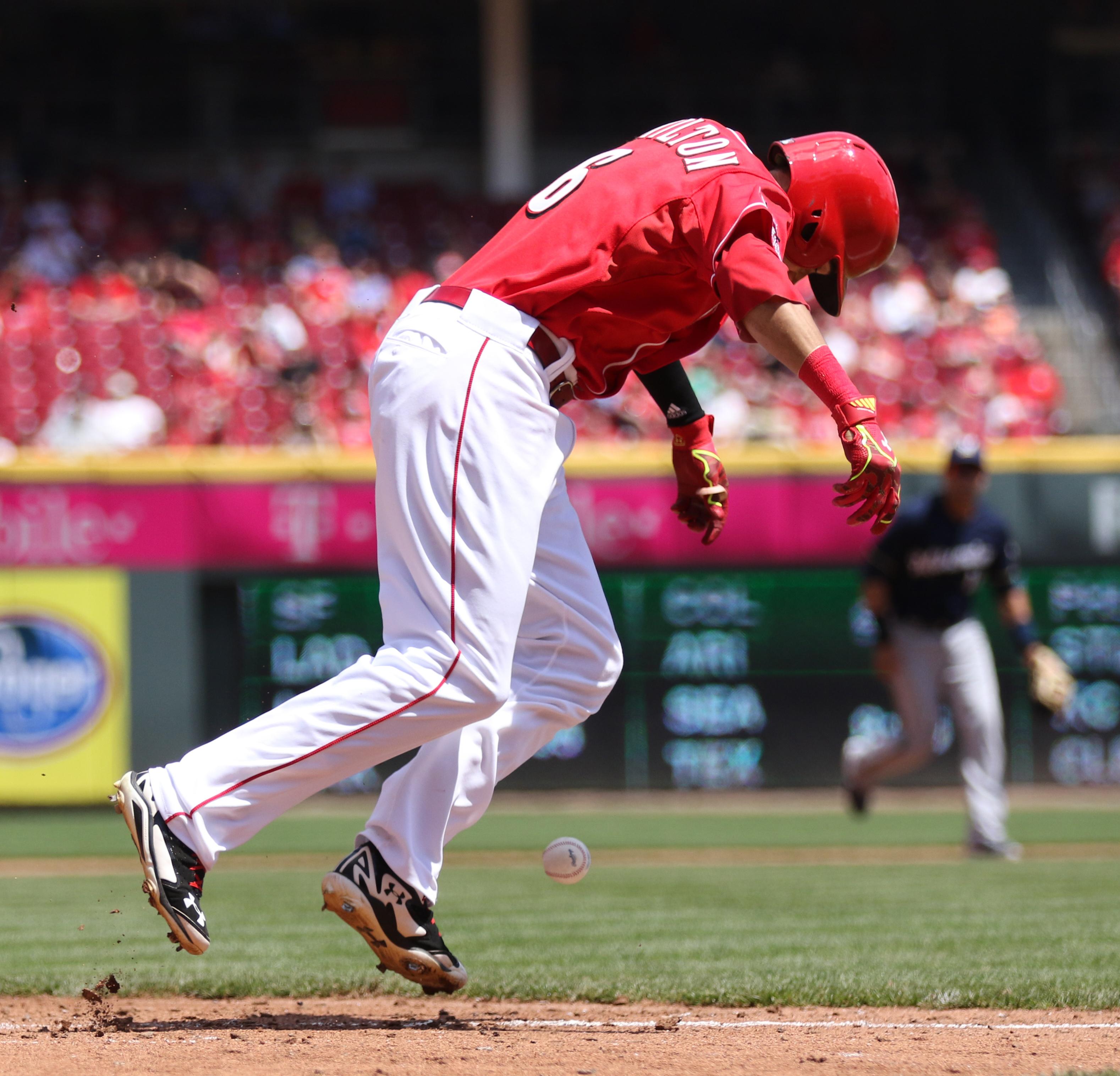 Cincinnati Reds'  Billy Hamilton (6) leaps over the baseball, a foul ball off his bat, as he runs towards first base during the fifth inning of their baseball game against the Milwaukee Brewers played Wednesday, April 29, 2015 in Cincinnati. (AP Photo/Gar