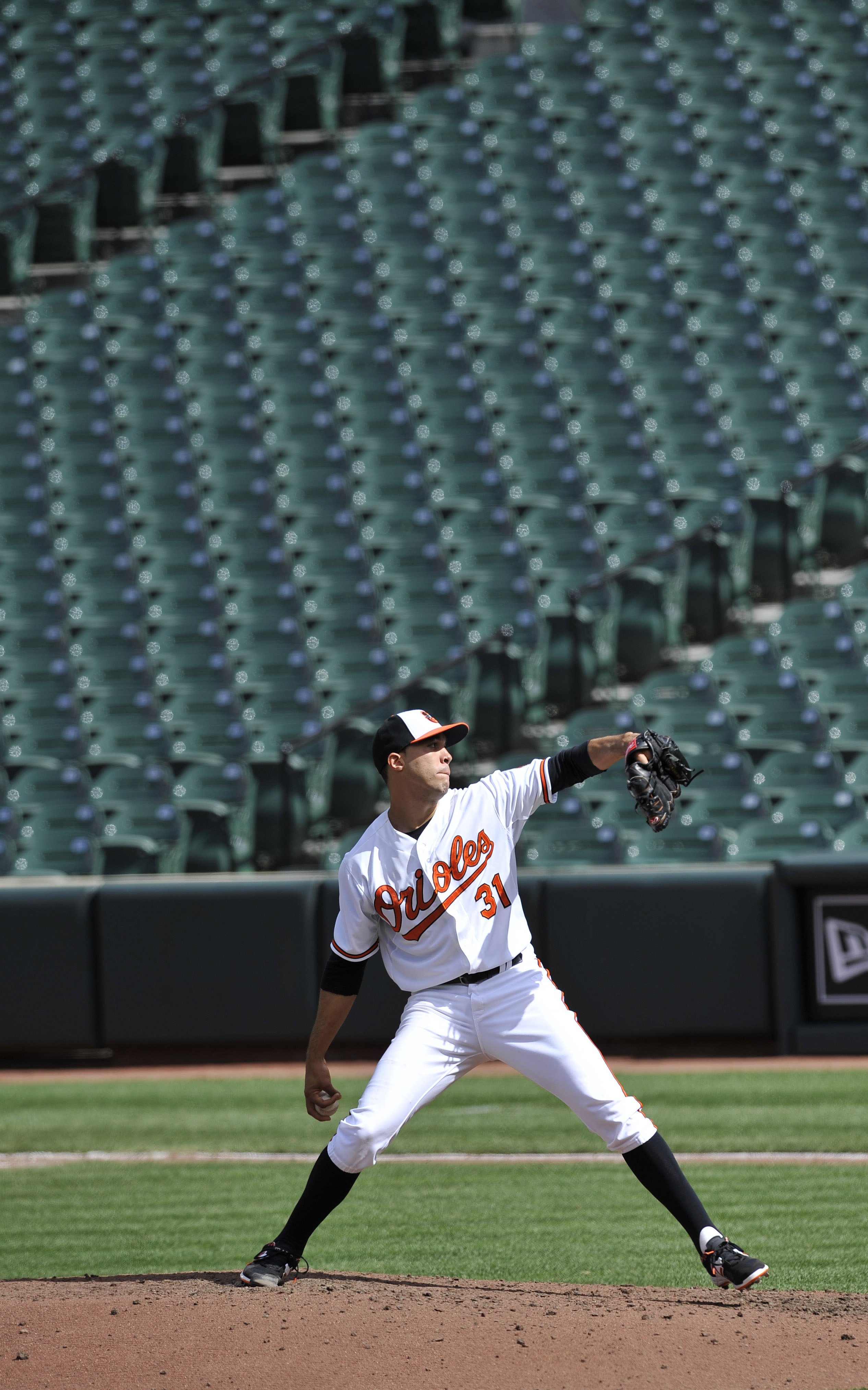 With a background of empty seats, Baltimore Orioles pitcher Ubaldo Jimenez throws against the Chicago White Sox during the fifth inning of a baseball game, Wednesday, April 29, 2015, in Baltimore. Due to security concerns the game was closed to the public