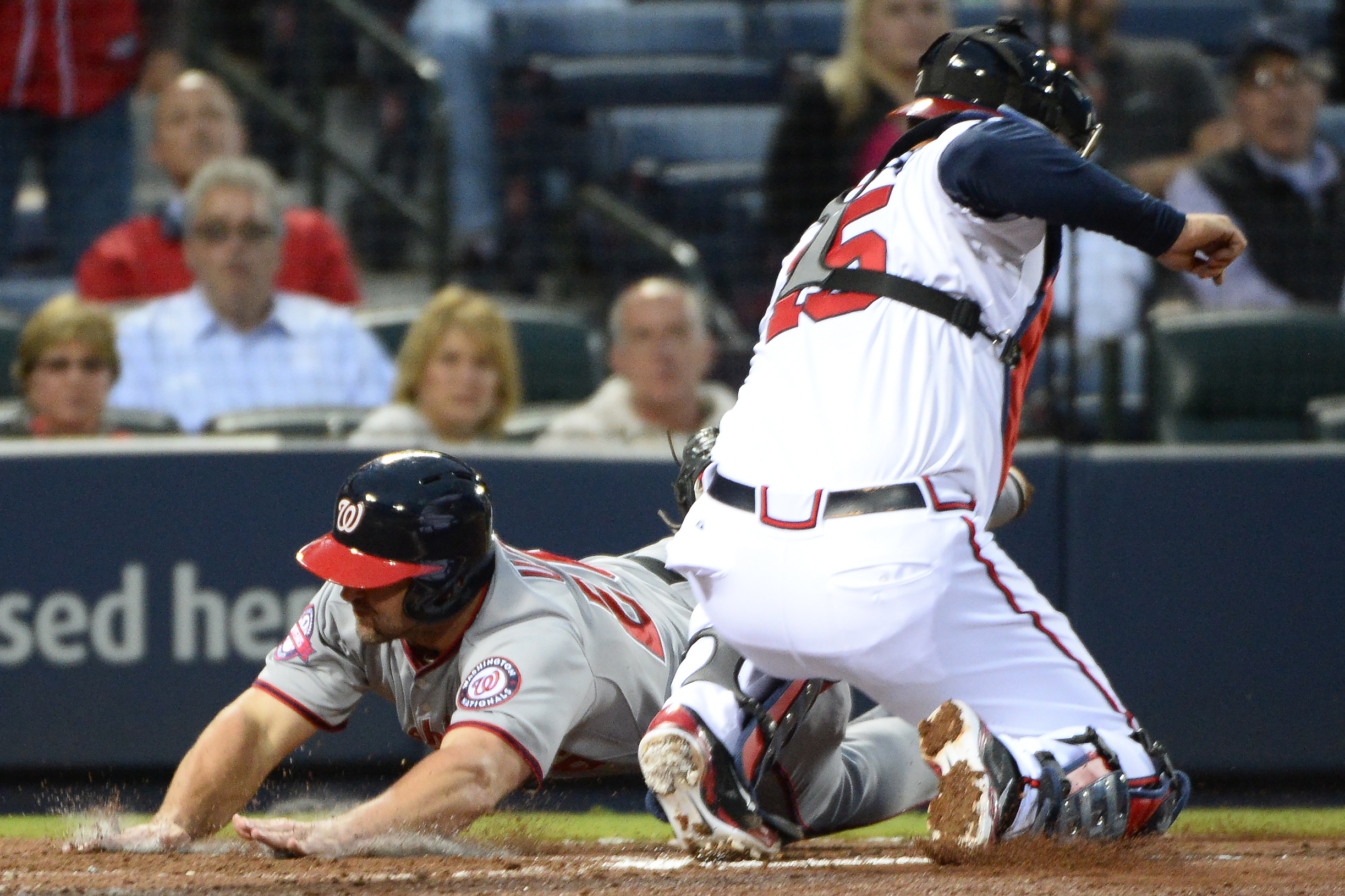 Washington Nationals' Dan Uggla, left, scores past Atlanta Braves catcher A.J. Pierzynski (15) on a three-run single by pitcher Jordan Zimmermann during the fourth inning inning of a baseball game Wednesday, April 29, 2015, in Atlanta. (AP Photo/David Tul