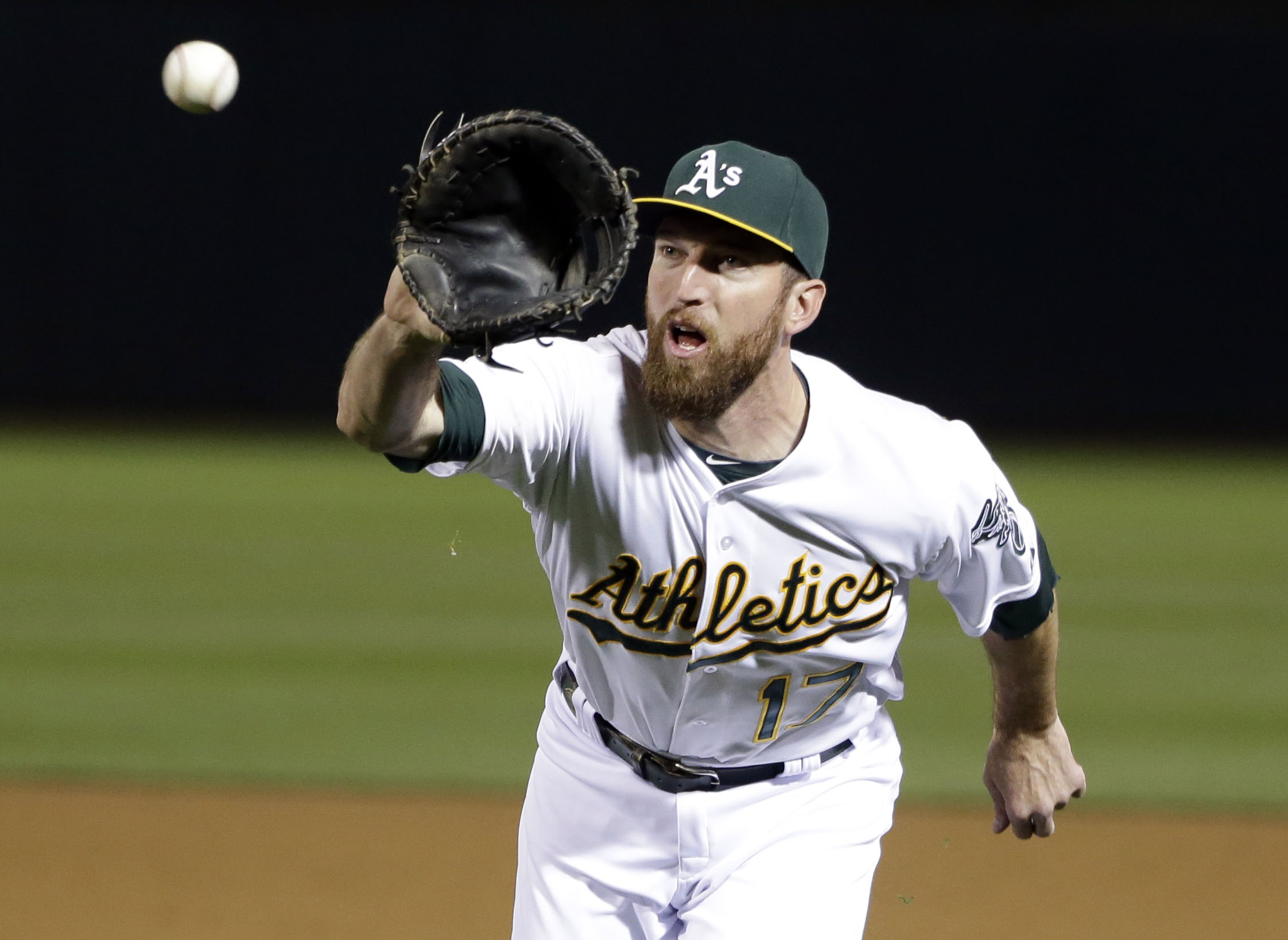 Oakland Athletics first baseman Ike Davis (17) makes a catch on a bunt attempt from Los Angeles Angels' Grant Green during the seventh inning of a baseball game Wednesday, April 29, 2015, in Oakland, Calif. (AP Photo/Marcio Jose Sanchez)