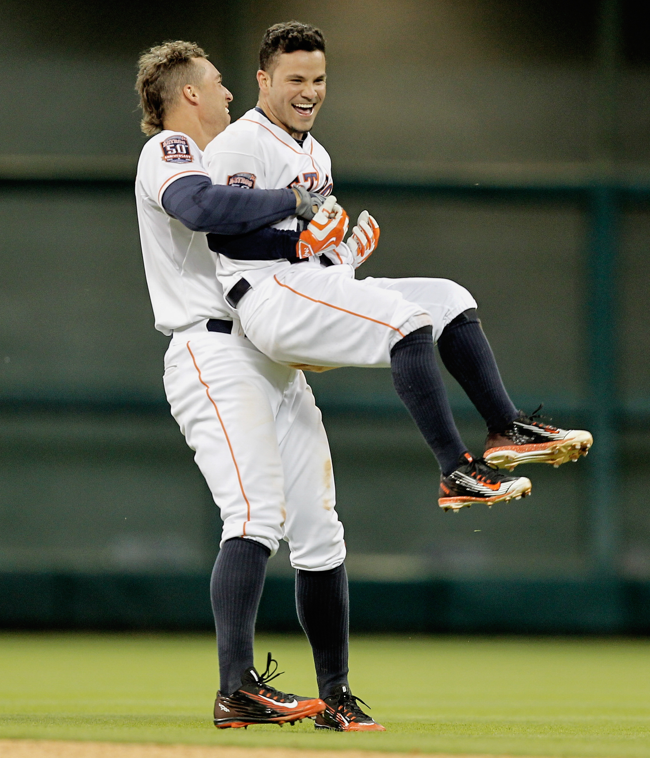 Houston Astros second baseman Jose Altuve (27), center, is grabbed by George Springer after singling in the winning run in the tenth inning against the Seattle Mariners in a baseball game Thursday April 30, 2015 in Houston. Houston won 3-2. (AP Photo/Bob