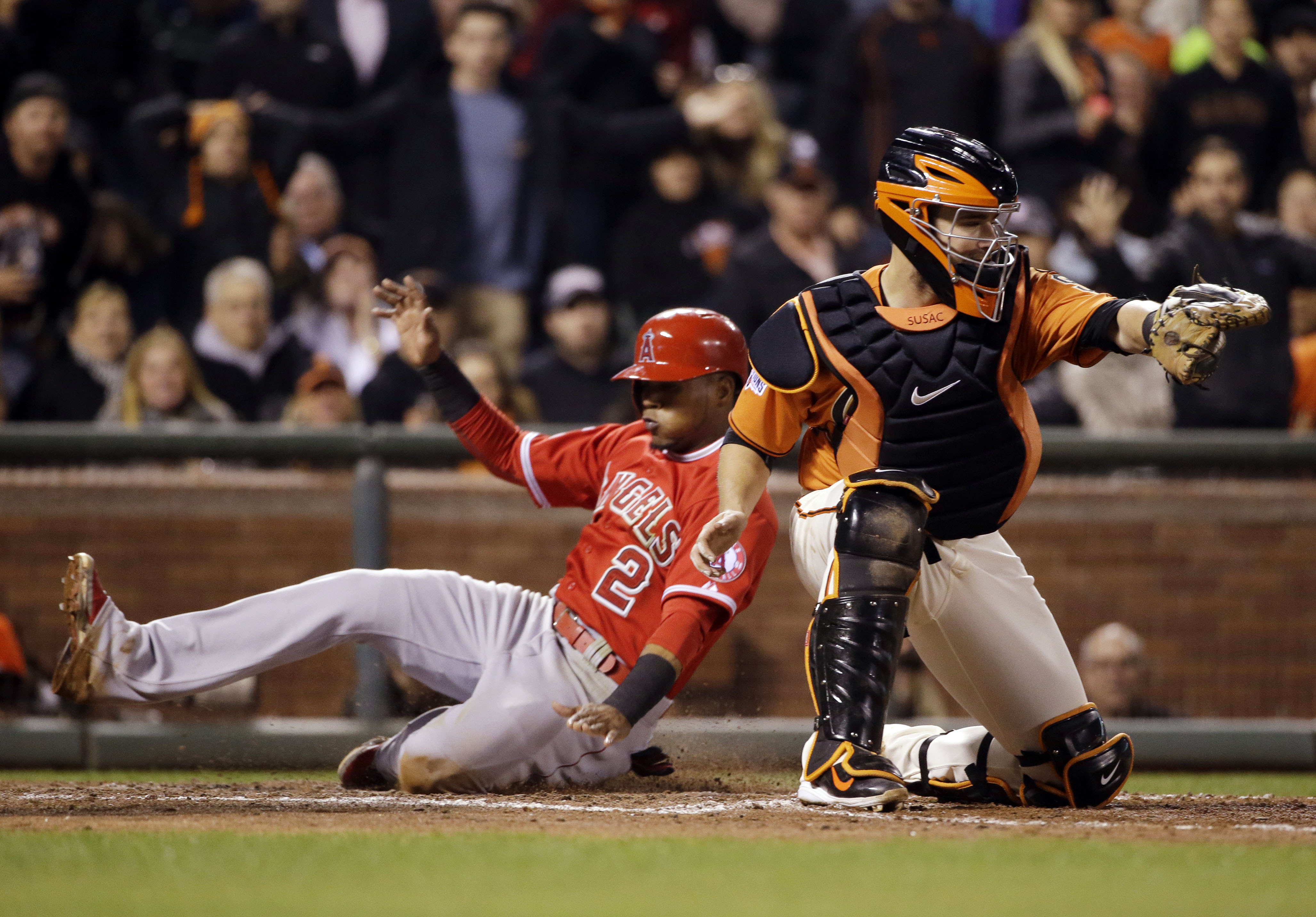 Los Angeles Angels' Erick Aybar (2) scores past San Francisco Giants catcher Andrew Susac on a sacrifice fly ball by David Freese during the eighth inning of a baseball game on Friday, May 1, 2015, in San Francisco. (AP Photo/Marcio Jose Sanchez)