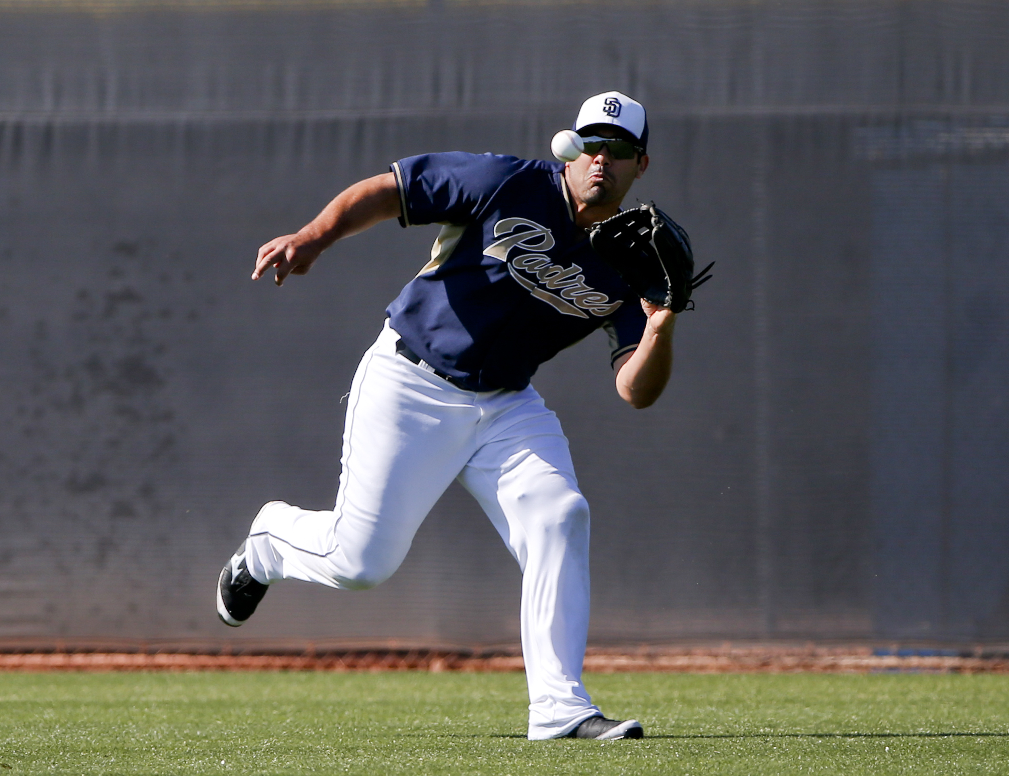 FILE- In this March 23, 2015, file photo, San Diego Padres left fielder Carlos Quentin runs down a line drive during fielding drills for outfielders prior to a spring training baseball game against the Chicago White Sox in Peoria, Ariz.  Quentin retired F
