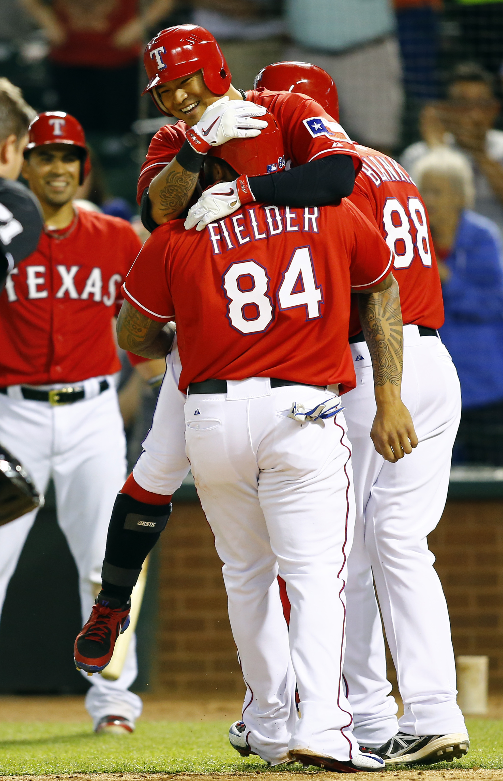 Texas Rangers' Prince Fielder (84) lifts Shin-Soo Choo after Choo hit a three-run home run to tie the game against the Oakland Athletics in the eighth inning of a baseball game Saturday, May 2, 2015, in Arlington, Texas. (AP Photo/Mike Stone)