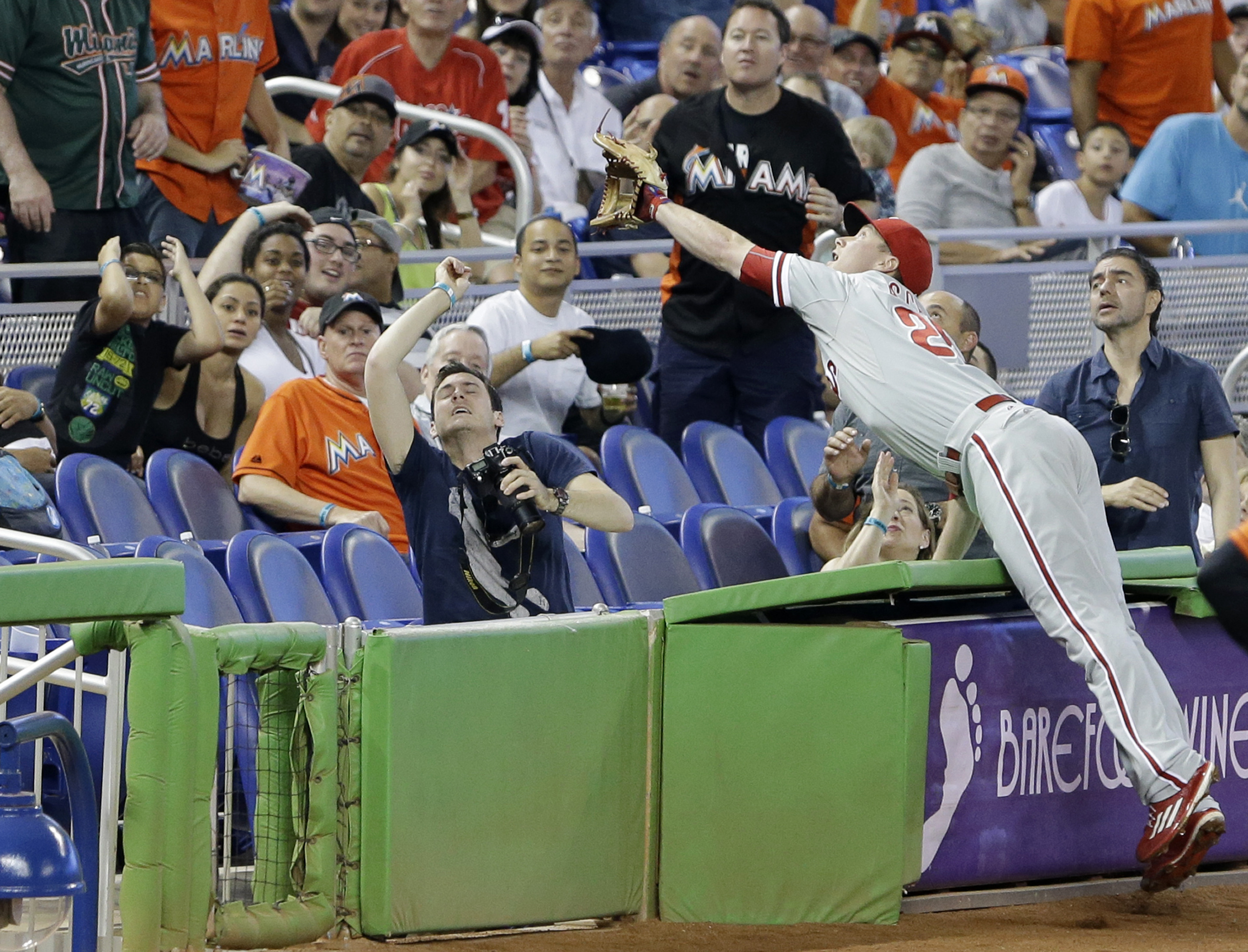 Philadelphia Phillies third baseman Cody Asche dives for a ball as he attempts to catch a foul hit by Miami Marlins' Adeiny Hechavarria during the fourth inning of a baseball game, Sunday, May 3, 2015, in Miami. (AP Photo/Wilfredo Lee)