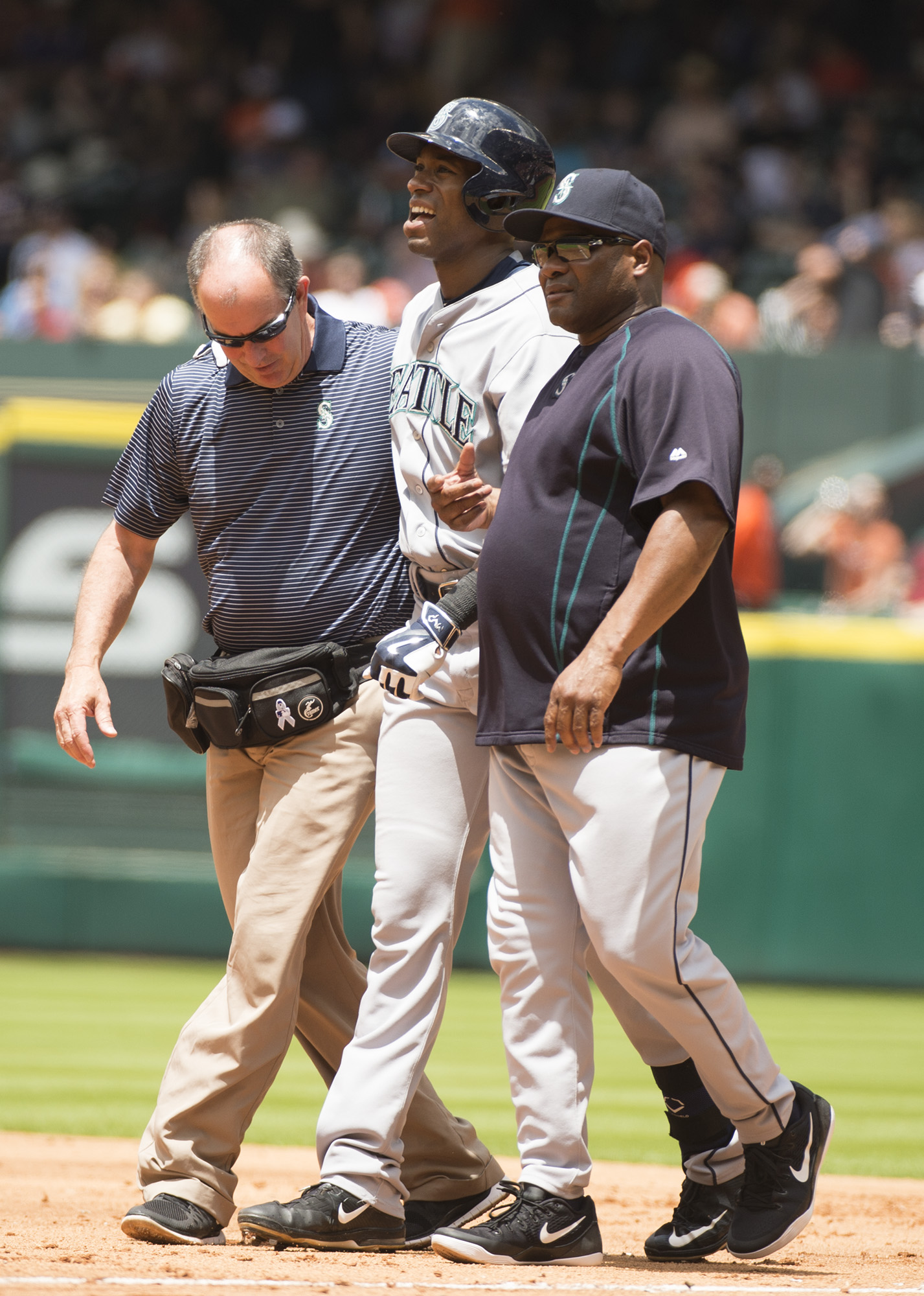 Seattle Mariners' Austin Jackson, center, is helped off the field by a trainer and first base coach Chris Woodward after a close play at first base against the Houston Astros in the third inning of a baseball game on Sunday, May 3, 2015, in Houston, Texas