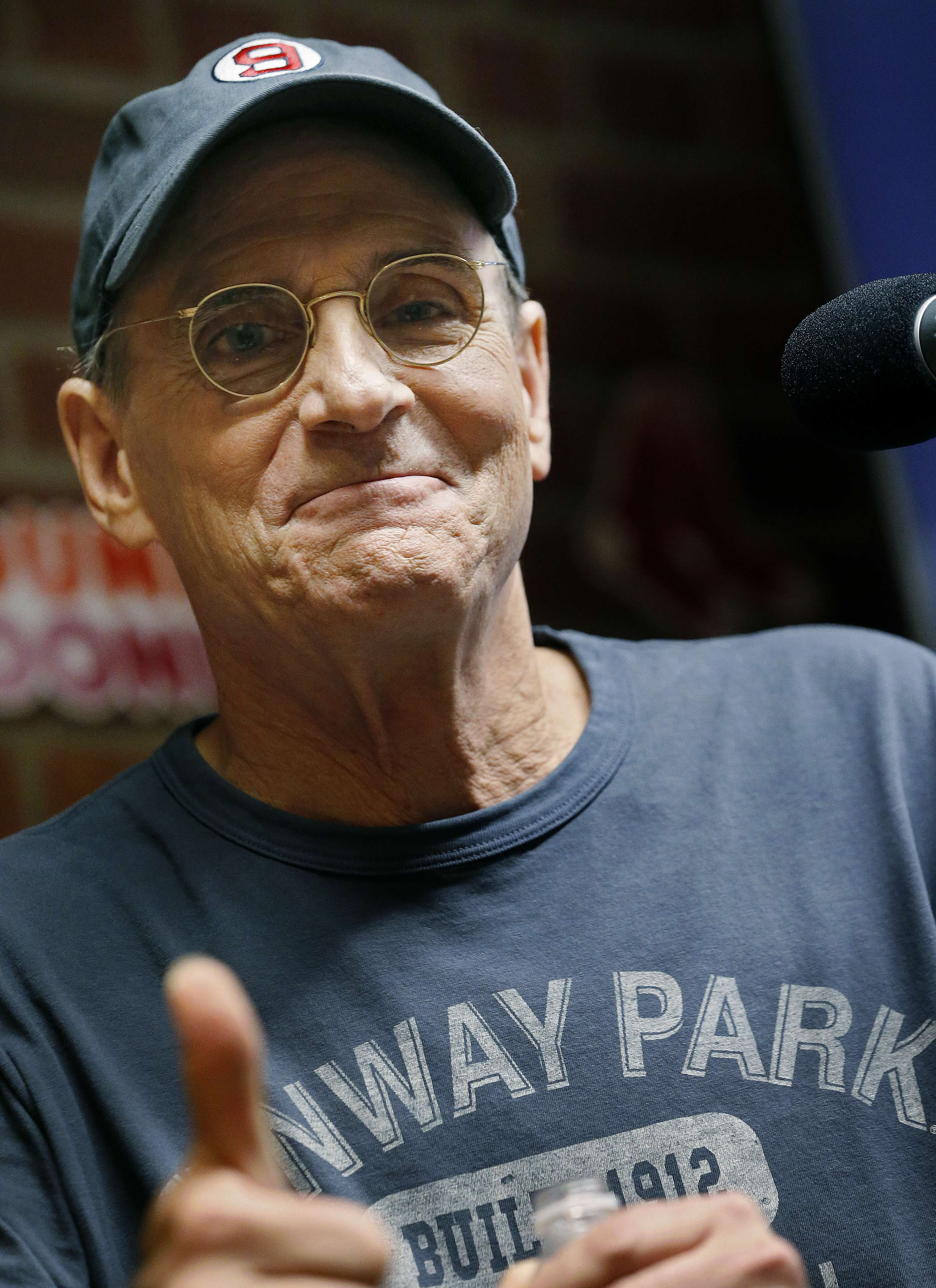 """James Taylor gives a thumbs-up during a news conference to promote his new song """"Angels of Fenway"""" about the Boston Red Sox before a baseball game between the Red Sox and the New York Yankees in Boston, Sunday, May 3, 2015. (AP Photo/Michael Dwyer)"""