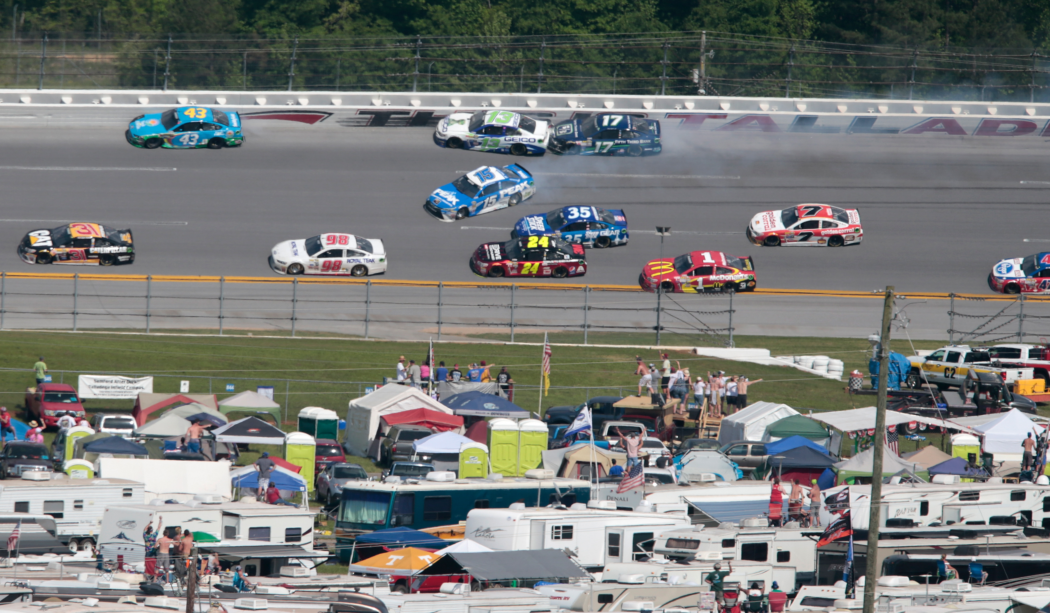 Casey Mears (13) and Ricky Stenhouse Jr. (17) crash on the final lap while Clint Bowyer (15) spins past them during the Talladega 500 NASCAR Sprint Cup Series auto race at Talladega Superspeedway, Sunday, May 3, 2015, in Talladega, Ala. (AP Photo/Butch Di