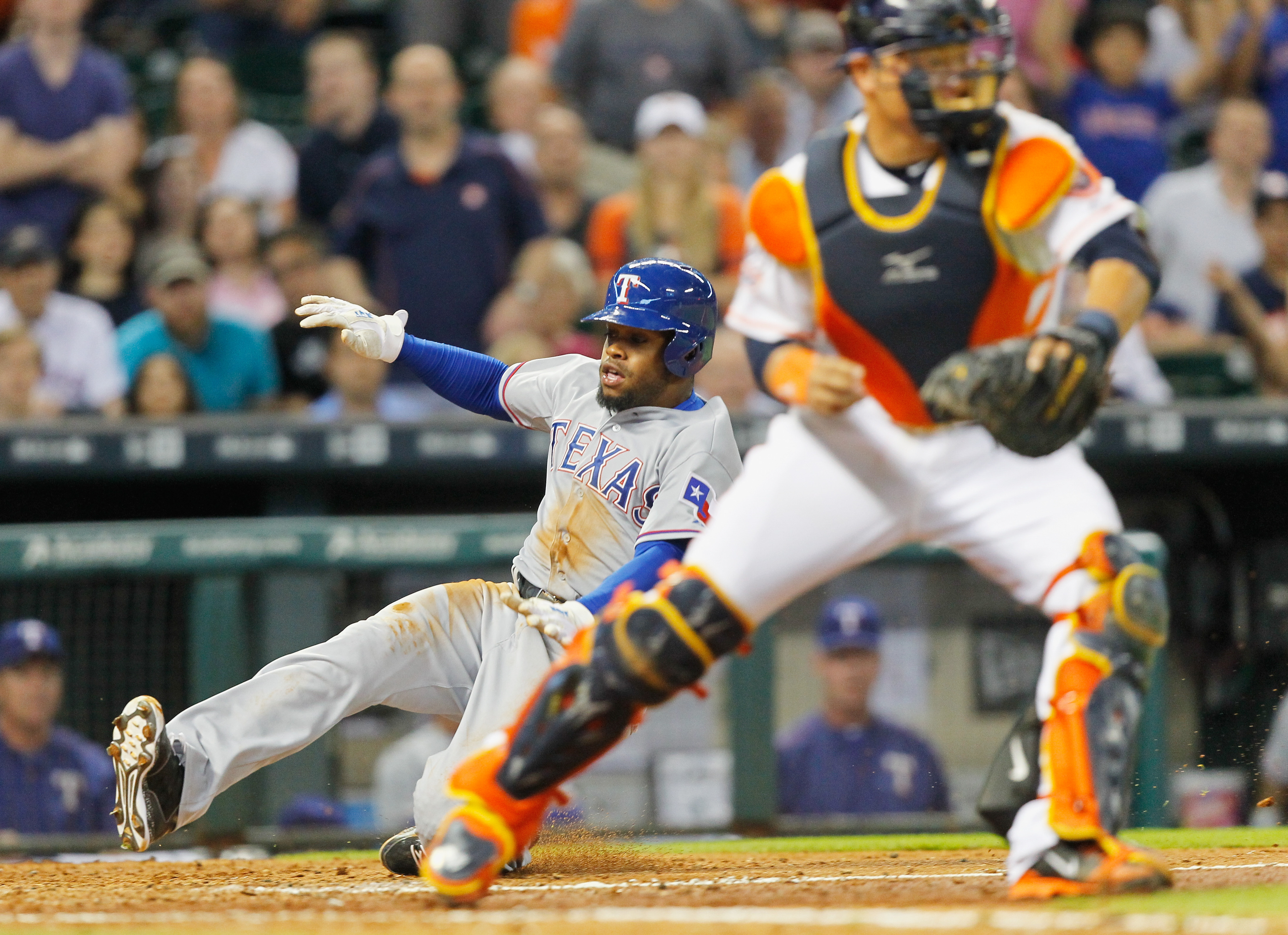 Texas Rangers'  Delino DeShields Jr. (7) scores on a single by Jake Smolinski in the eighth inning as Houston Astros catcher Hank Conger (16) awaits the throw in a baseball game Monday May 4, 2015, in Houston. (AP Photo/Bob Levey)