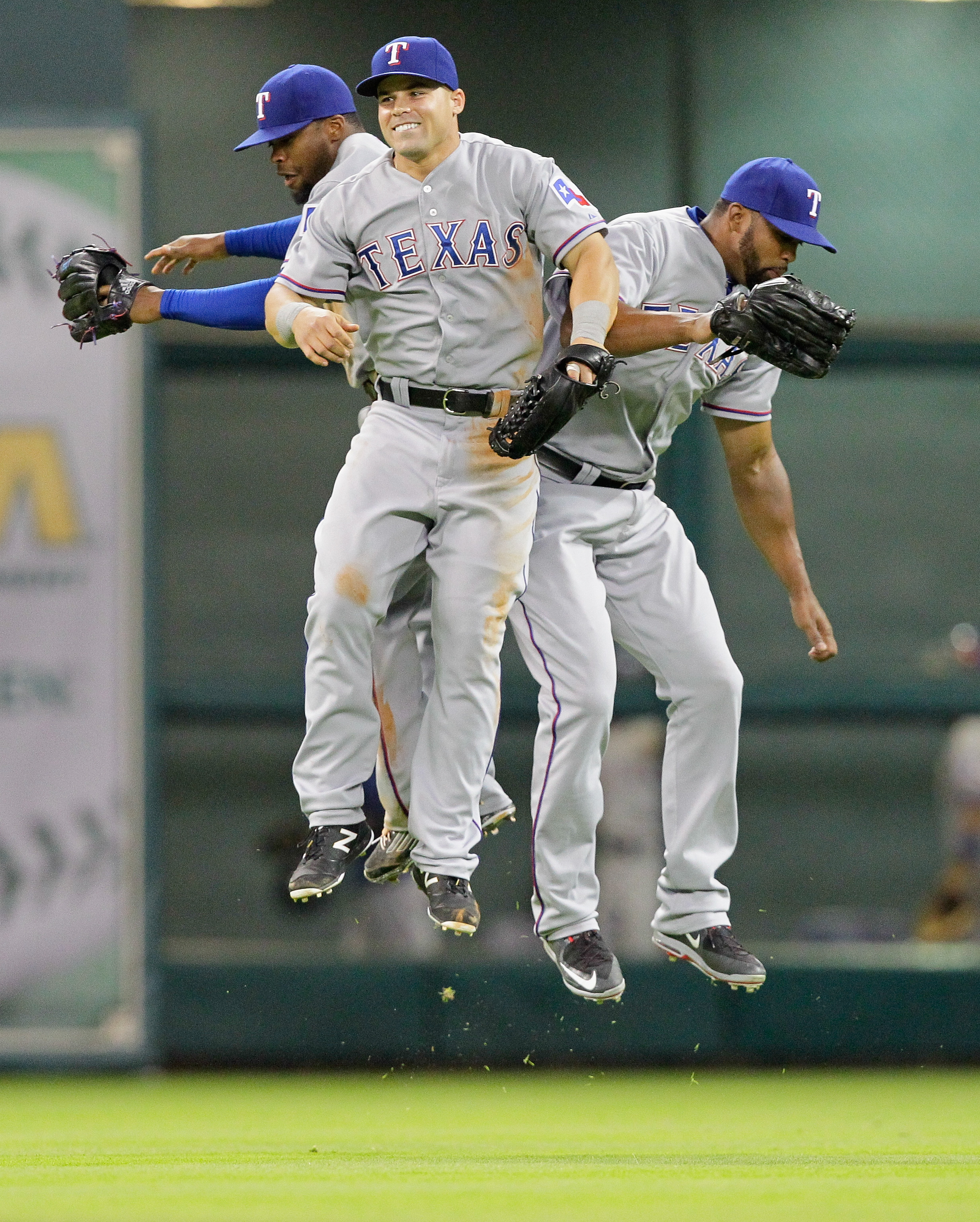 Texas Rangers' Jake Smolinski, center, along with left fielder Carlos Peguero, right, Delino DeShields Jr., left, celebrate after the final out against the Houston Astros in a baseball game Monday May 4, 2015 in Houston. Texas Rangers won 2-1. (AP Photo/B
