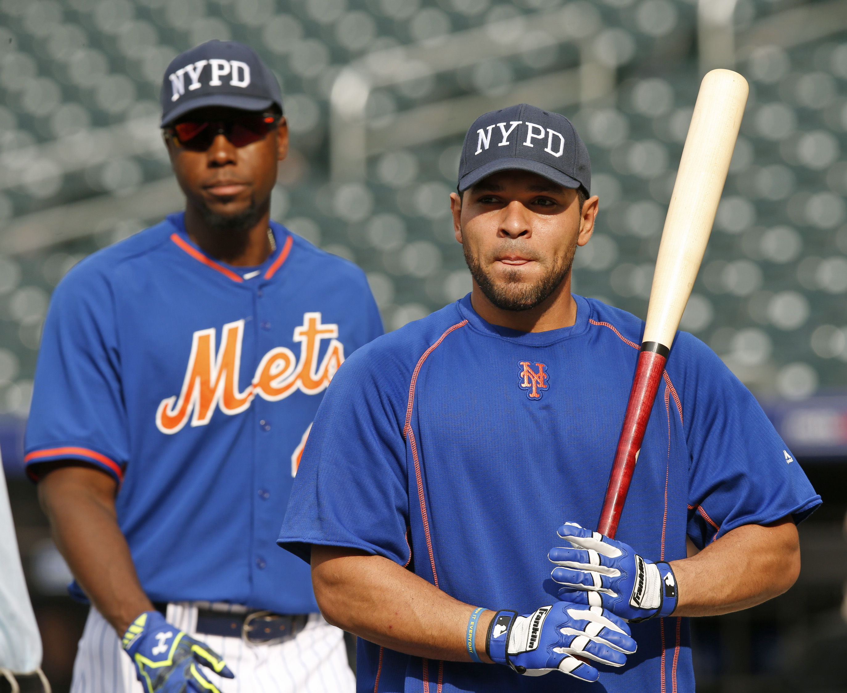 New York Mets players, including John Mayberry Jr., and Johnny Monell, wear New York Police Department hats in memory of slain New York City police officer Brian Moore before a baseball game against the Baltimore Orioles in New York, Tuesday, May 5, 2015.