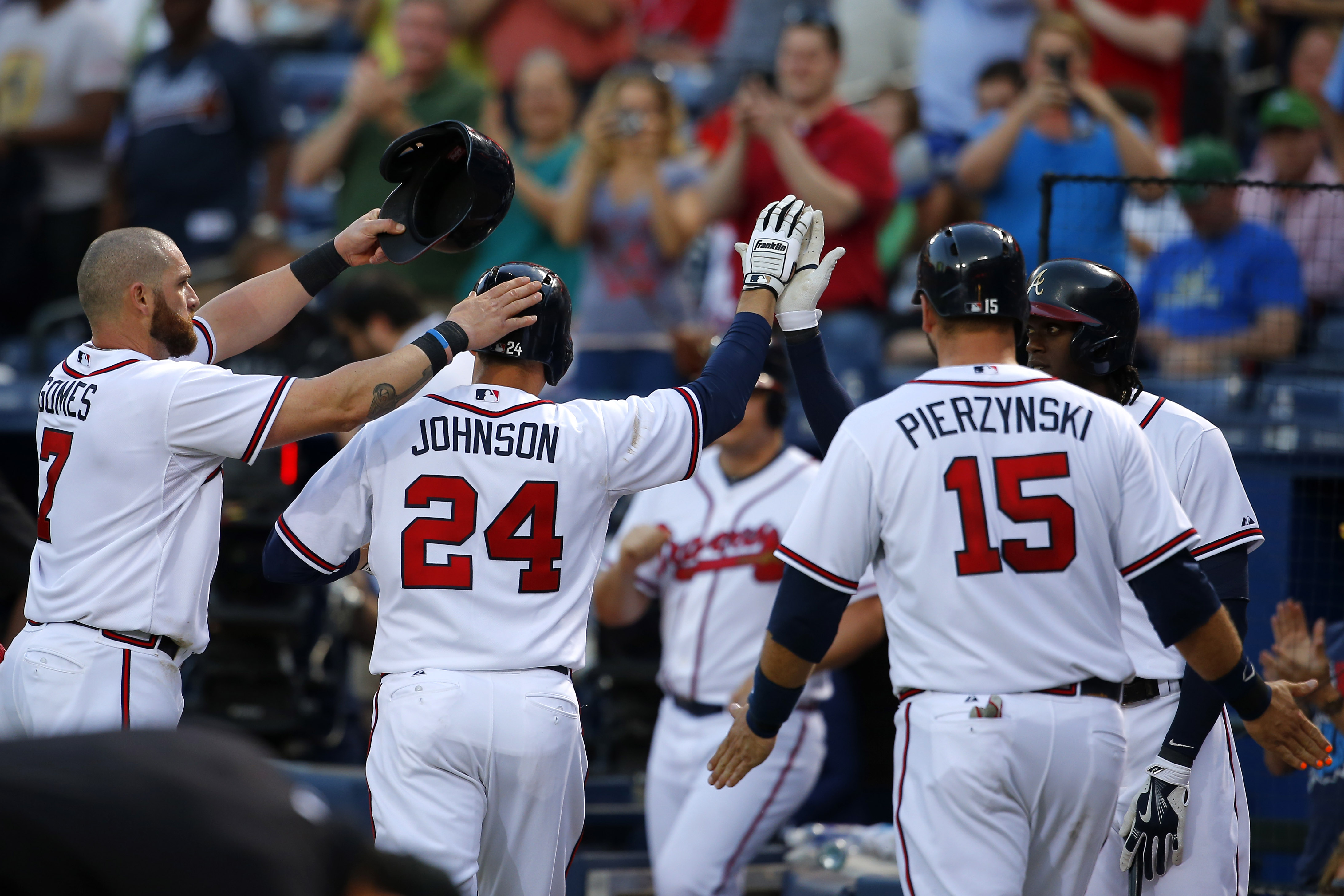 Atlanta Braves' Kelly Johnson (24) celebrates his three-run homer with Jonny Gomes, left, A.J. Pierzynski (15) and center fielder Cameron Maybin, right, in the fourth inning of a baseball game against the Philadelphia Phillies, Tuesday, May 5, 2015, in At