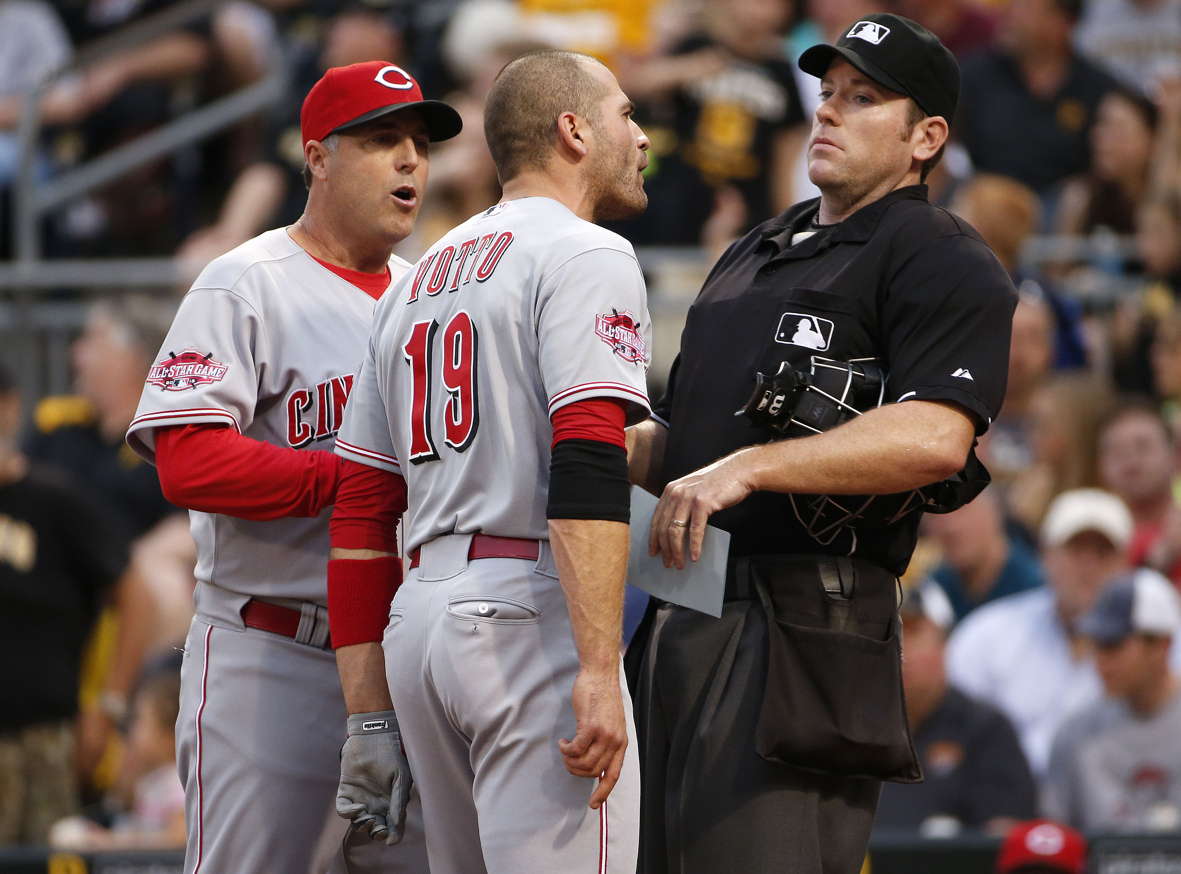 Cincinnati Reds' Joey Votto (19) bumps into umpire Chris Conroy, right, as he talks with Reds manager Bryan Price, left, during the third inning of a baseball game against the Pittsburgh Pirates, Wednesday, May 6, 2015, in Pittsburgh. Votto was ejected fr