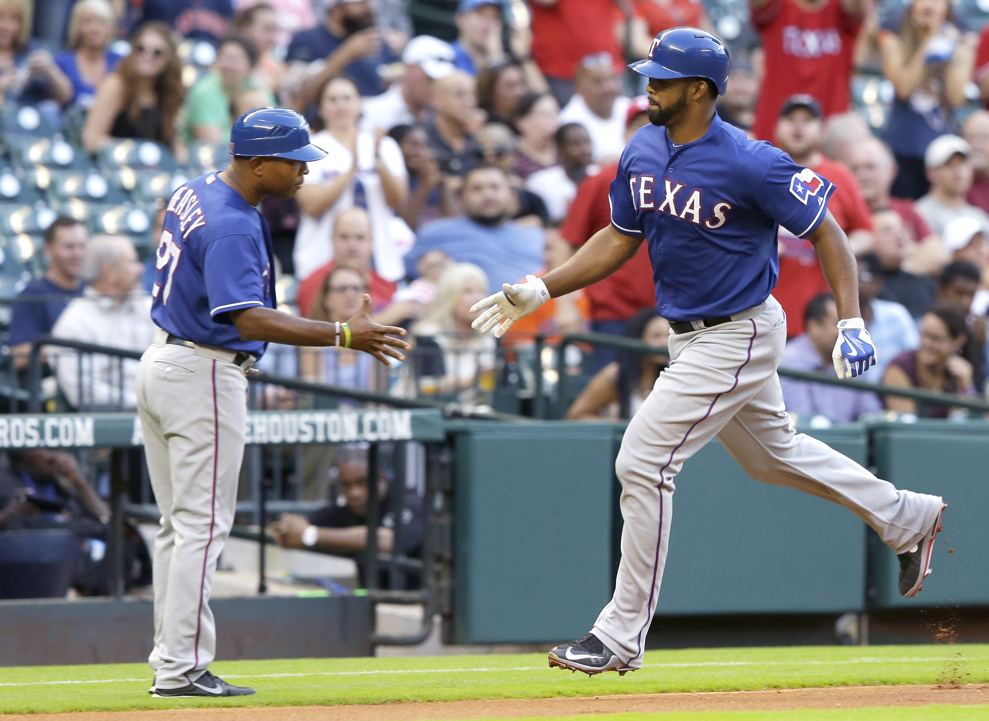 Texas Rangers' Carlos Peguero, right, is congratulated by third base coach Tony Beasley as he rounds the bases on a solo homer against the Houston Astros during the second inning of a baseball game Wednesday, May 6, 2015, in Houston. (AP Photo/Pat Sulliva