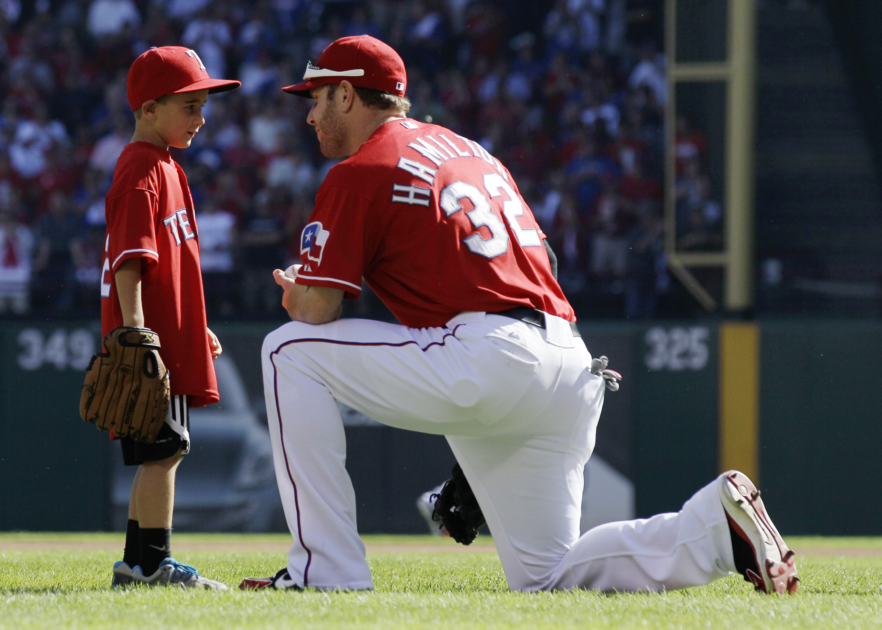 ADVANCE FOR WEEKEND EDITIONS, MAY 8-10 - FILE - In this Sept. 30, 2011, file photo, CooperStone, 6, talks with Texas Rangers left fielder Josh Hamilton after throwing out a ceremonial first pitch, before Game 1 of baseball's American League division serie