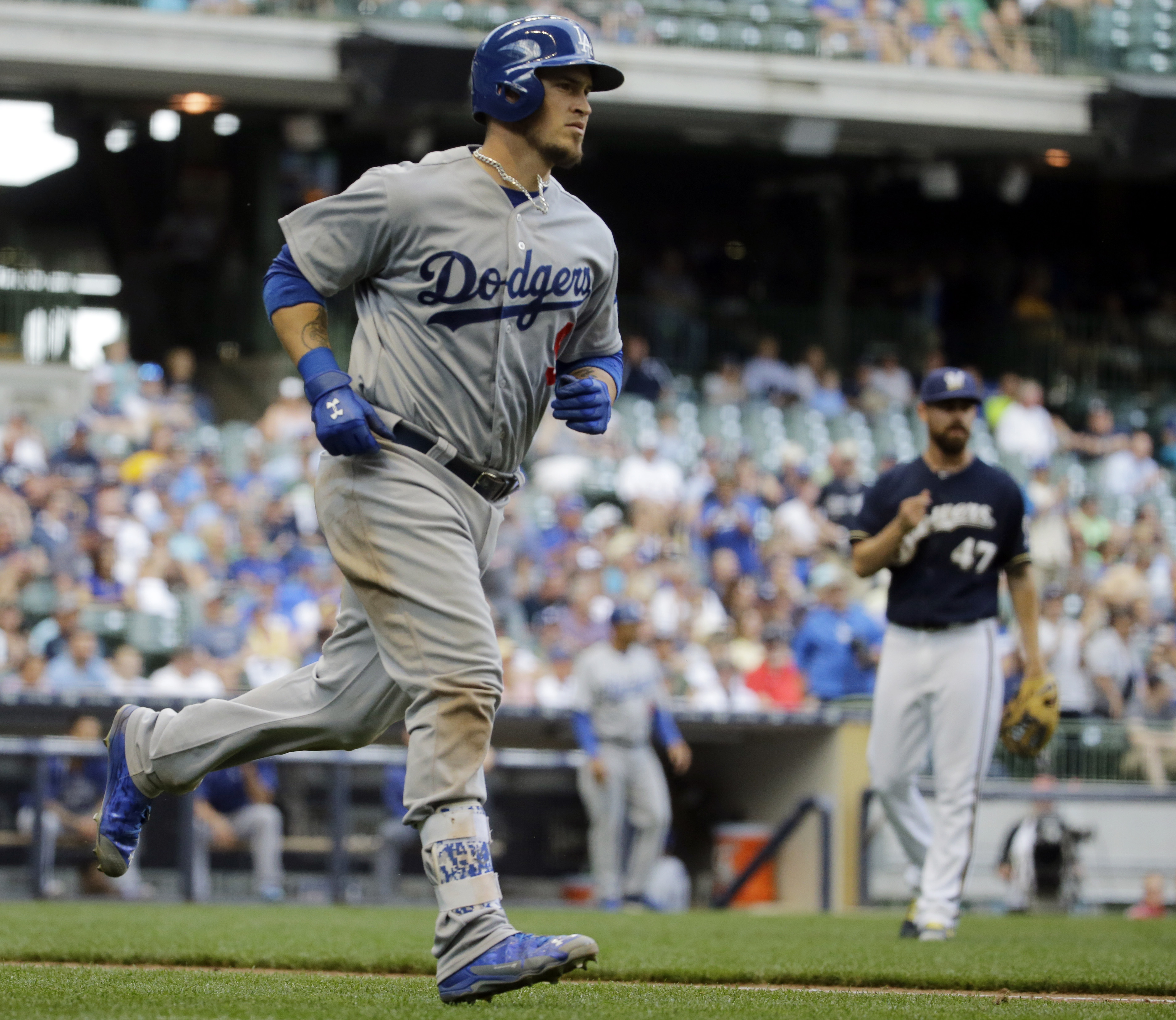 Milwaukee Brewers relief pitcher Rob Wooten (47) watches as Los Angeles Dodgers' Yasmani Grandal rounds the bases after hitting a three-run home run during the eighth inning of a baseball game Thursday, May 7, 2015, in Milwaukee. (AP Photo/Morry Gash)