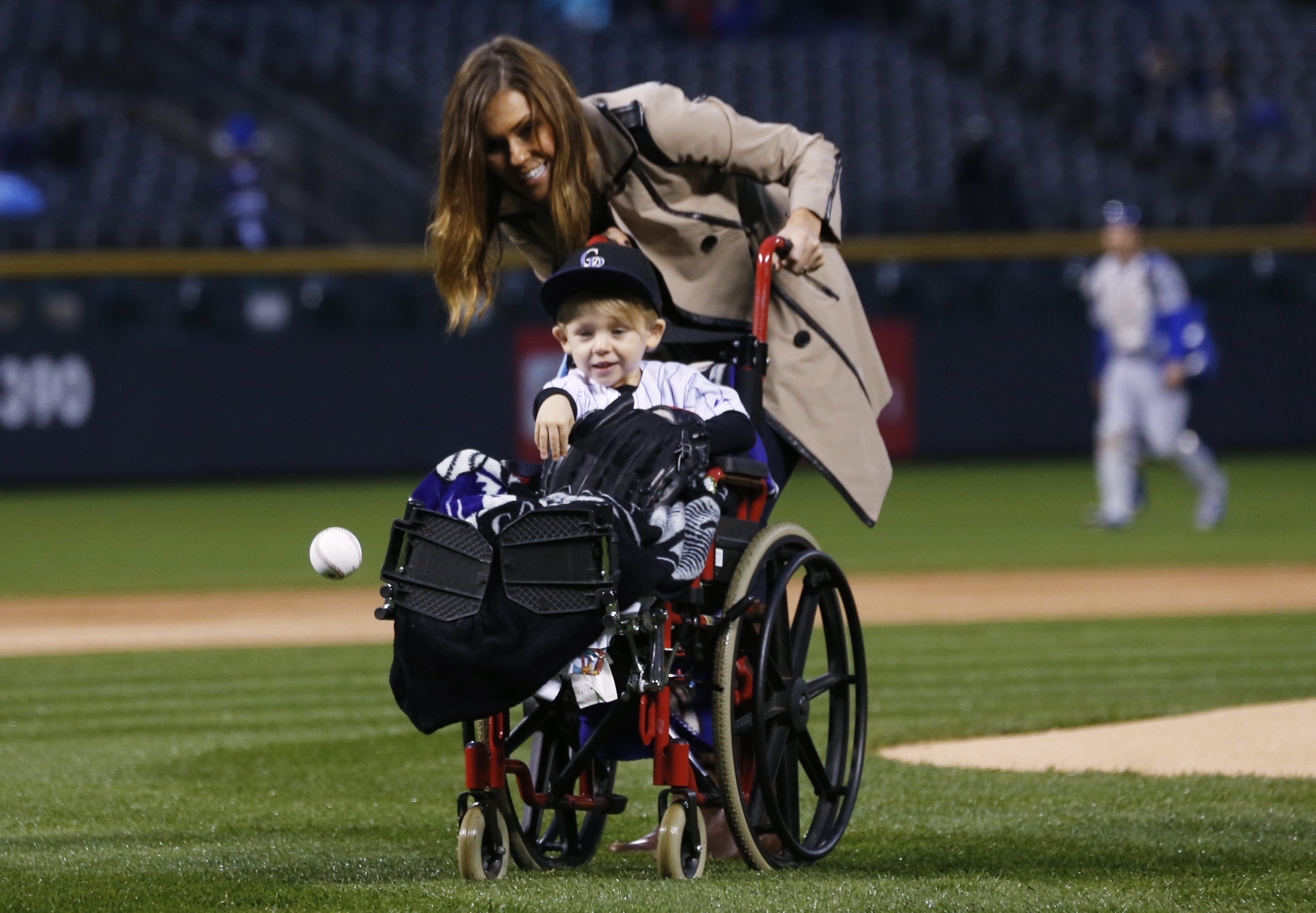 Two-year-old Jameson Axford throws out the ceremonial first pitch as his mother, Nicole, looks on before the Colorado Rockies host the Los Angeles Dodgers in a baseball game Friday, May 8, 2015, in Denver. The little boy is the youngest son of Rockies rel