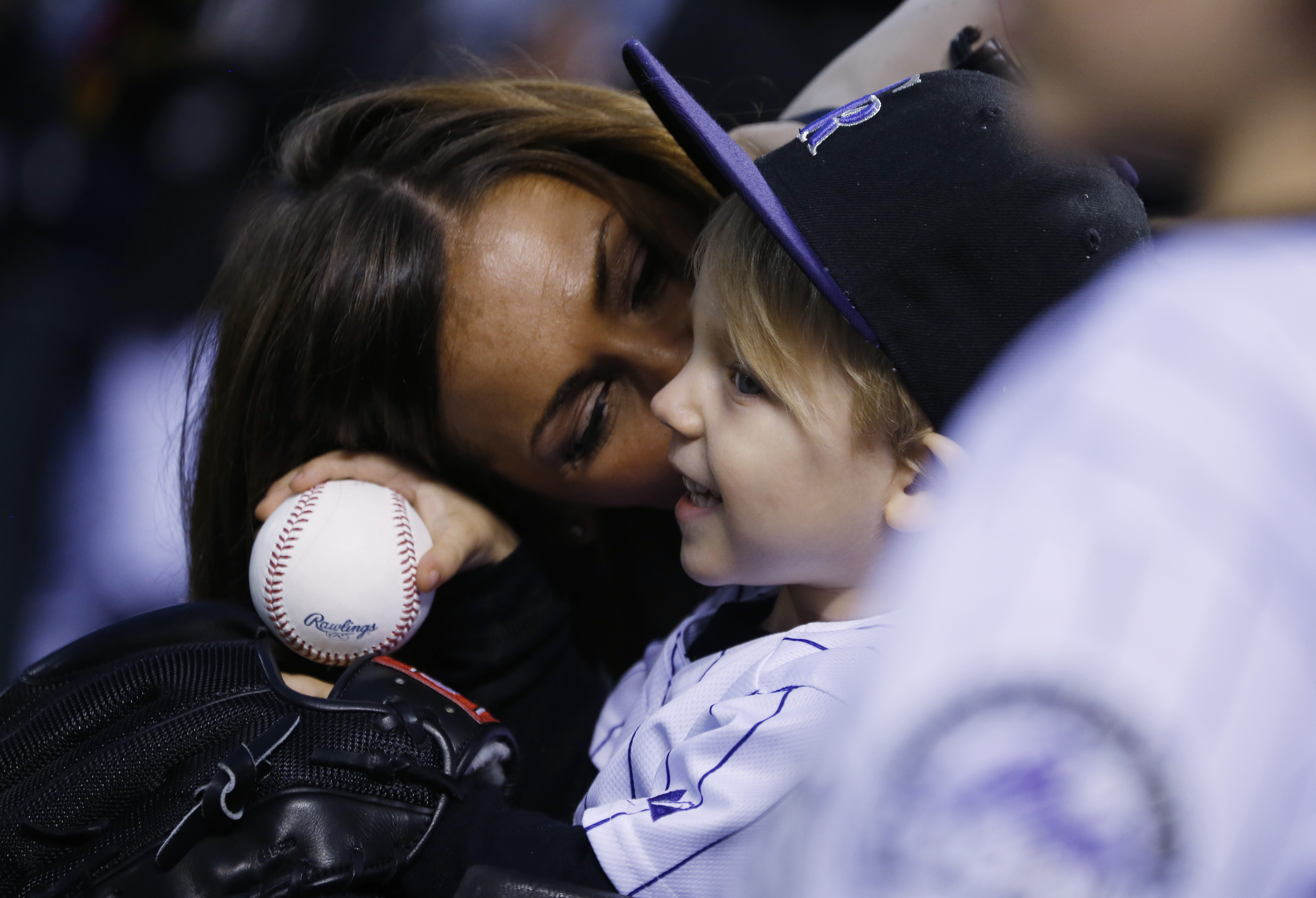 Nicole Axford, back, kisses her 2-year-old son, Jameson, as he waits to throw out the ceremonial first pitch before the Colorado Rockies host the Los Angeles Dodgers in a baseball game Friday, May 8, 2015, in Denver. The little boy, who is the son of Rock