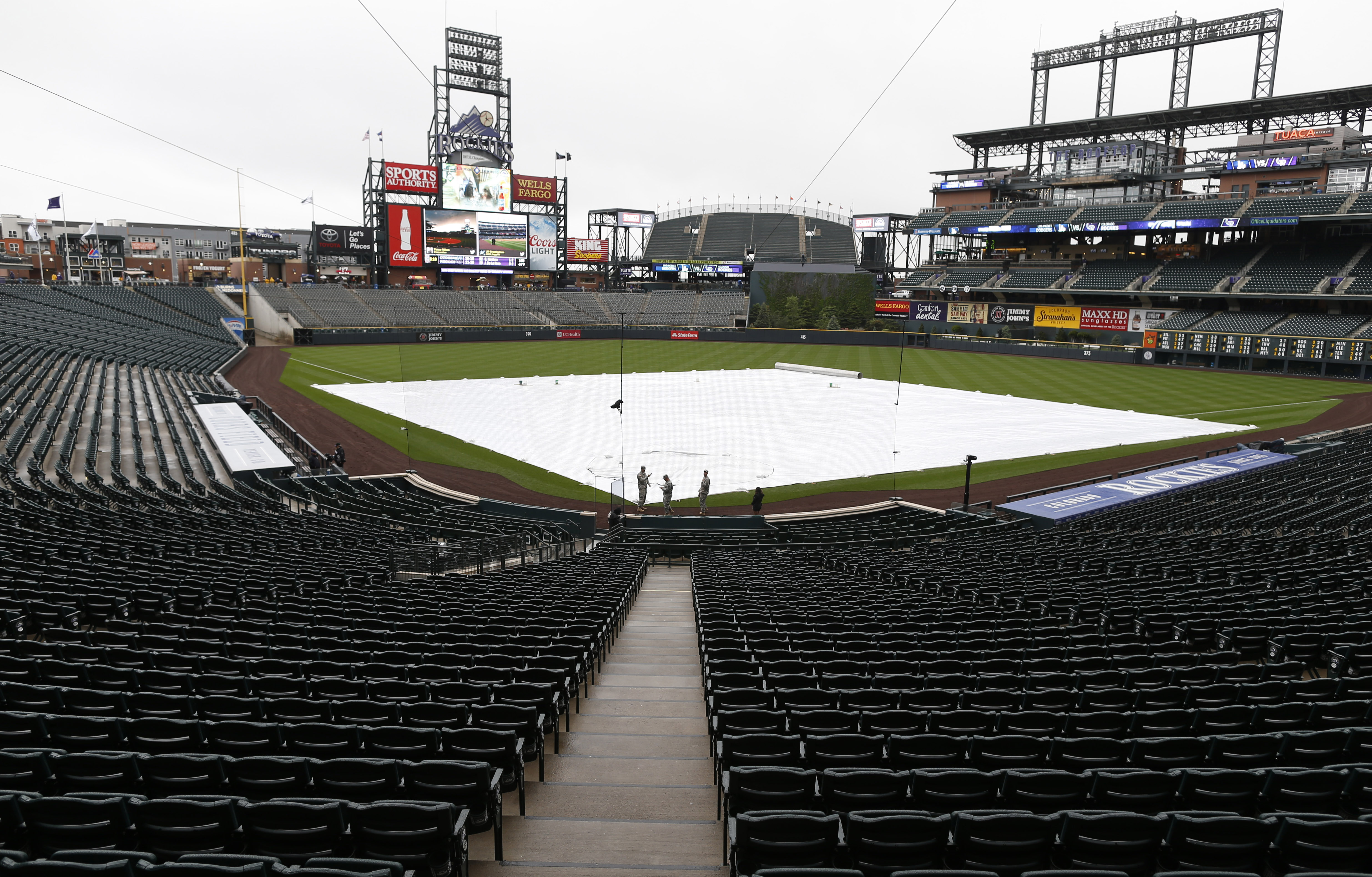 Stands sit empty and the diamond is covered by a tarpaulin in Coors Field after the cancellation of a baseball game between the Los Angeles Dodgers and the Colorado Rockies, Saturday, May 9, 2015, in Denver. Forecasters are predicting three to five inches