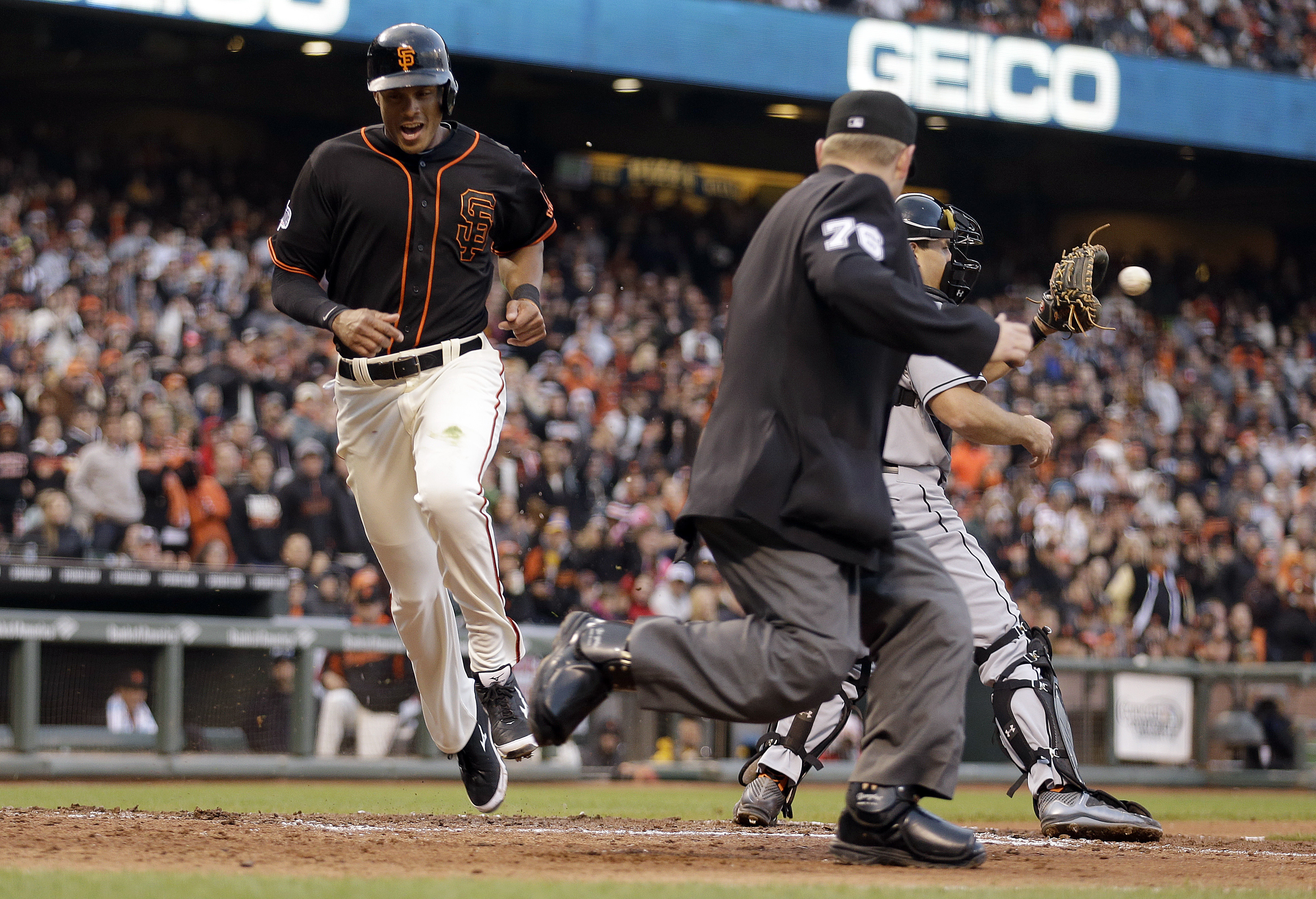 San Francisco Giants' Justin Maxwell, left, scores behind Miami Marlins catcher J.T. Realmuto, back right, in the fifth inning of a baseball game Saturday, May 9, 2015, in San Francisco. Maxwell scored on a single by Giants' Brandon Crawford. Home plate u