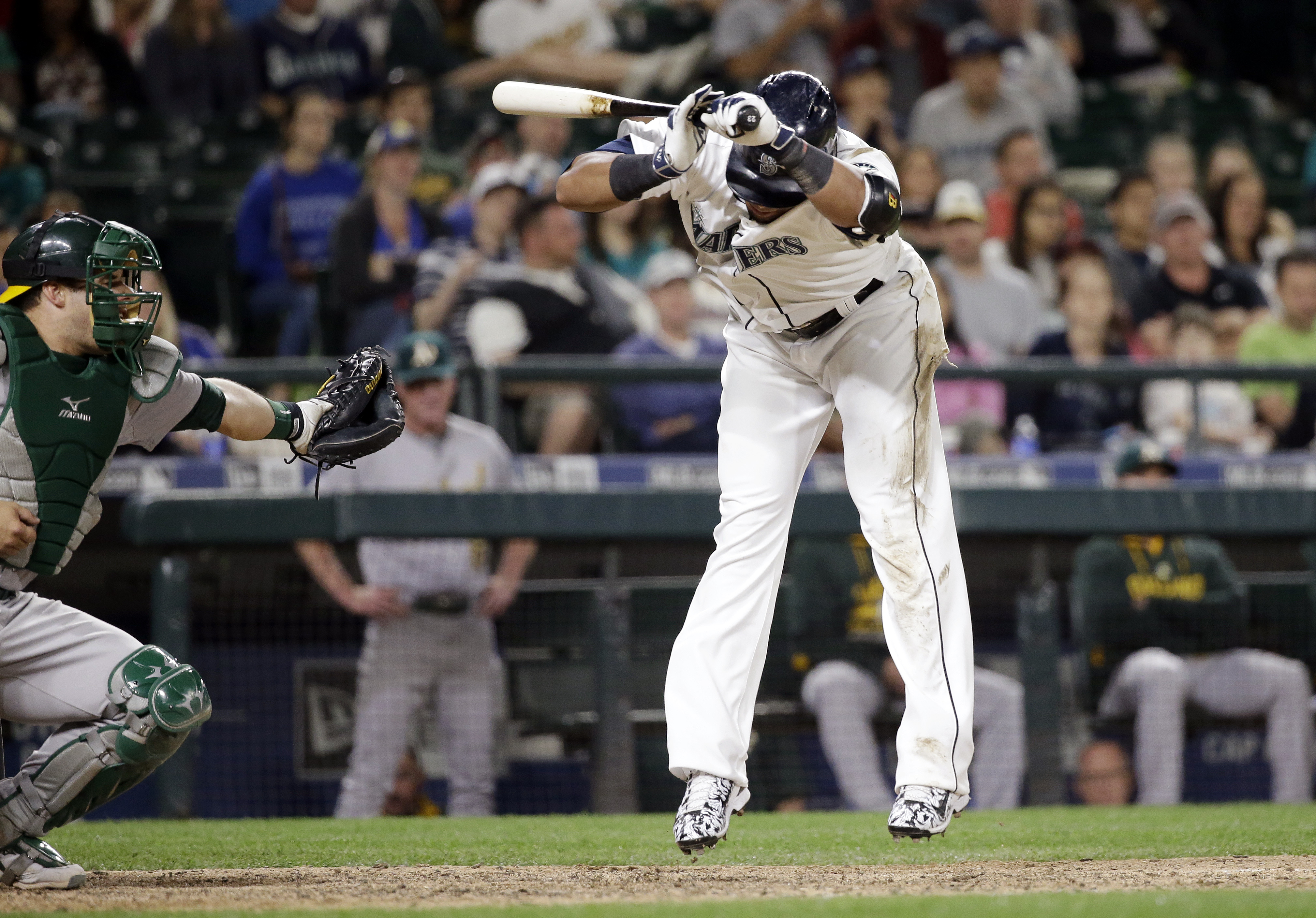 Seattle Mariners' Nelson Cruz, right, leaps back after being hit by a pitch as Oakland Athletics catcher Josh Phegley waits for the ball in the eighth inning of a baseball game Saturday, May 9, 2015, in Seattle. (AP Photo/Elaine Thompson)