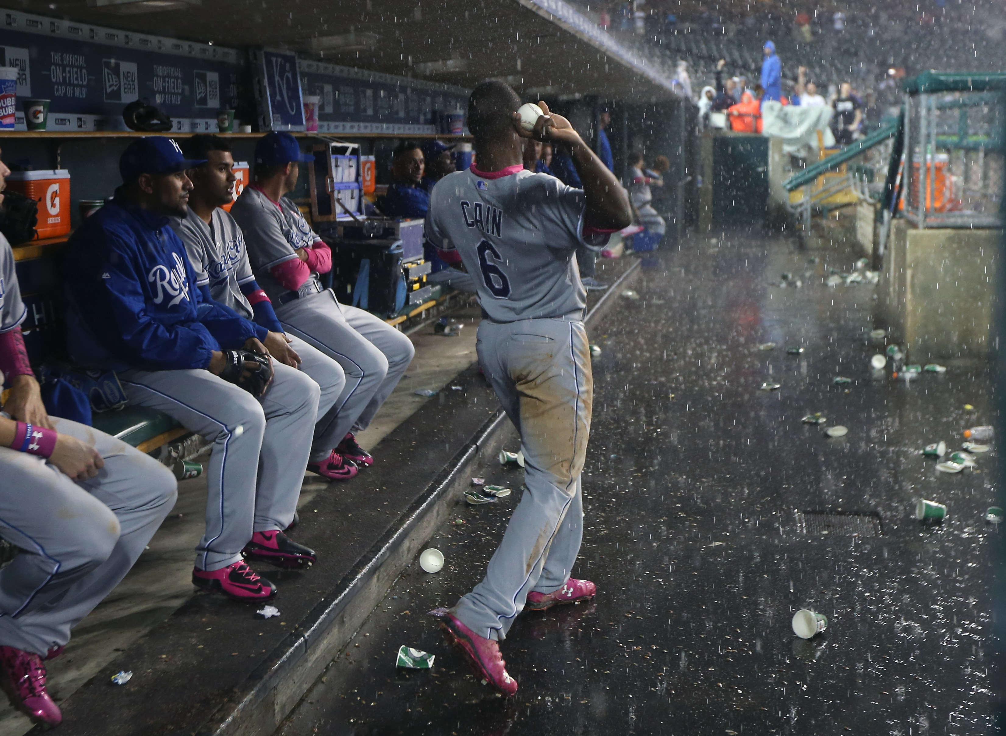 Kansas City Royals' Lorenzo Cain throws a ball to fans during a rain delay in the ninth inning of a baseball game against the Detroit Tigers, Sunday, May 10, 2015, in Detroit. (AP Photo/Carlos Osorio)