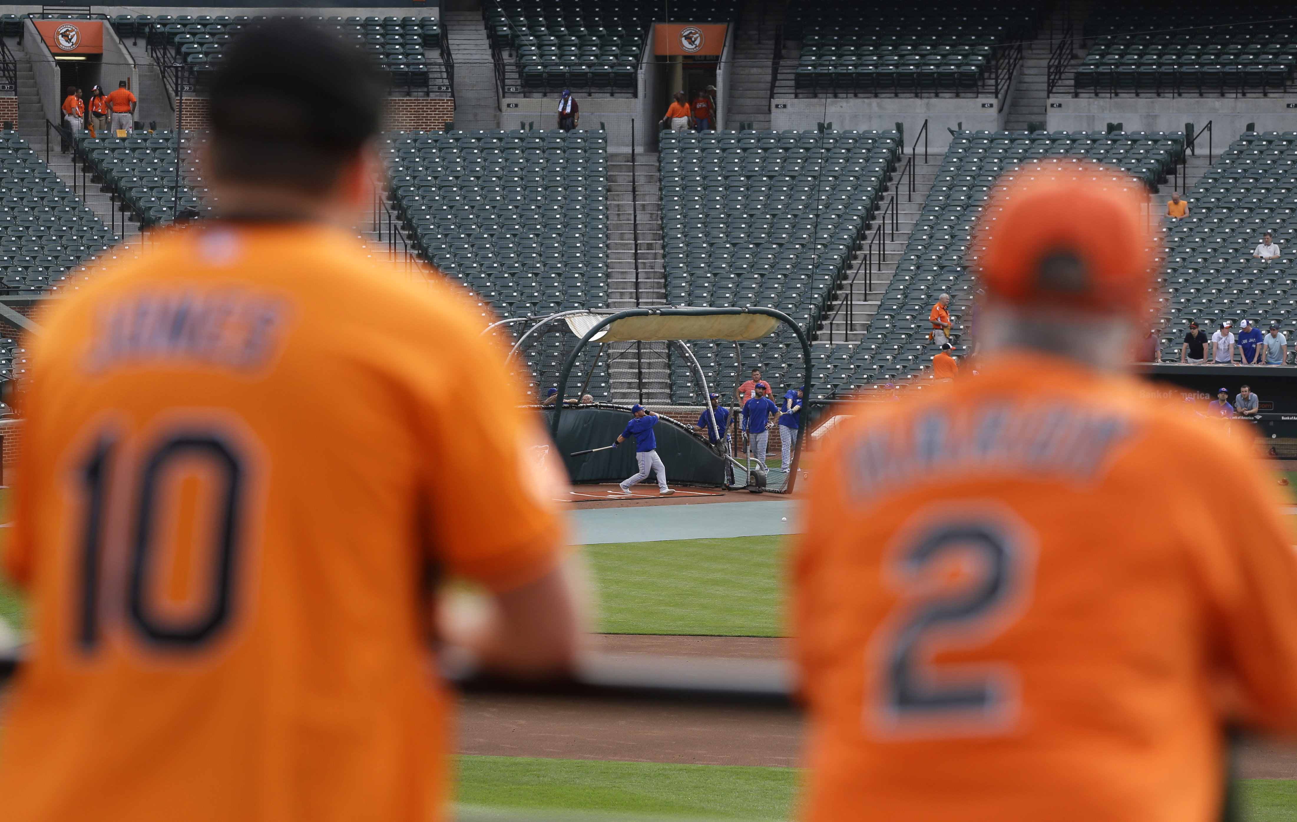 Baltimore Orioles fans watch members of the Toronto Blue Jays take batting practice before a baseball game between the Orioles and the Blue Jays, Monday, May 11, 2015, in Baltimore. Playing in front of their home fans for the first time in two weeks, the