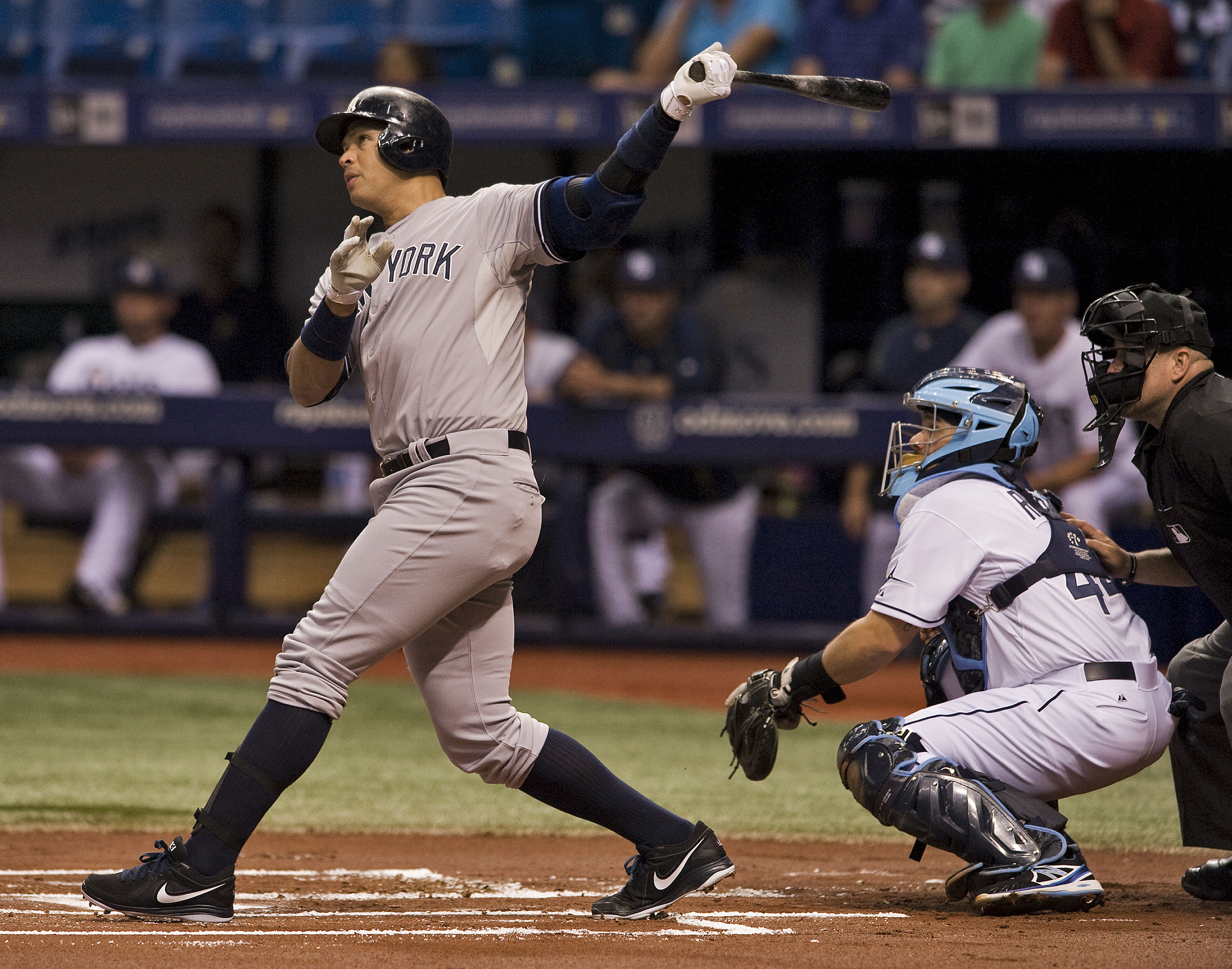 Tampa Bay Rays catcher Rene Rivera, center, and home plate umpire Adam Hamari, right, look on as New York Yankees designated hitter Alex Rodriguez hits a solo home run off Tampa Bay starter Alex Colome during the first inning of a baseball game Monday, Ma