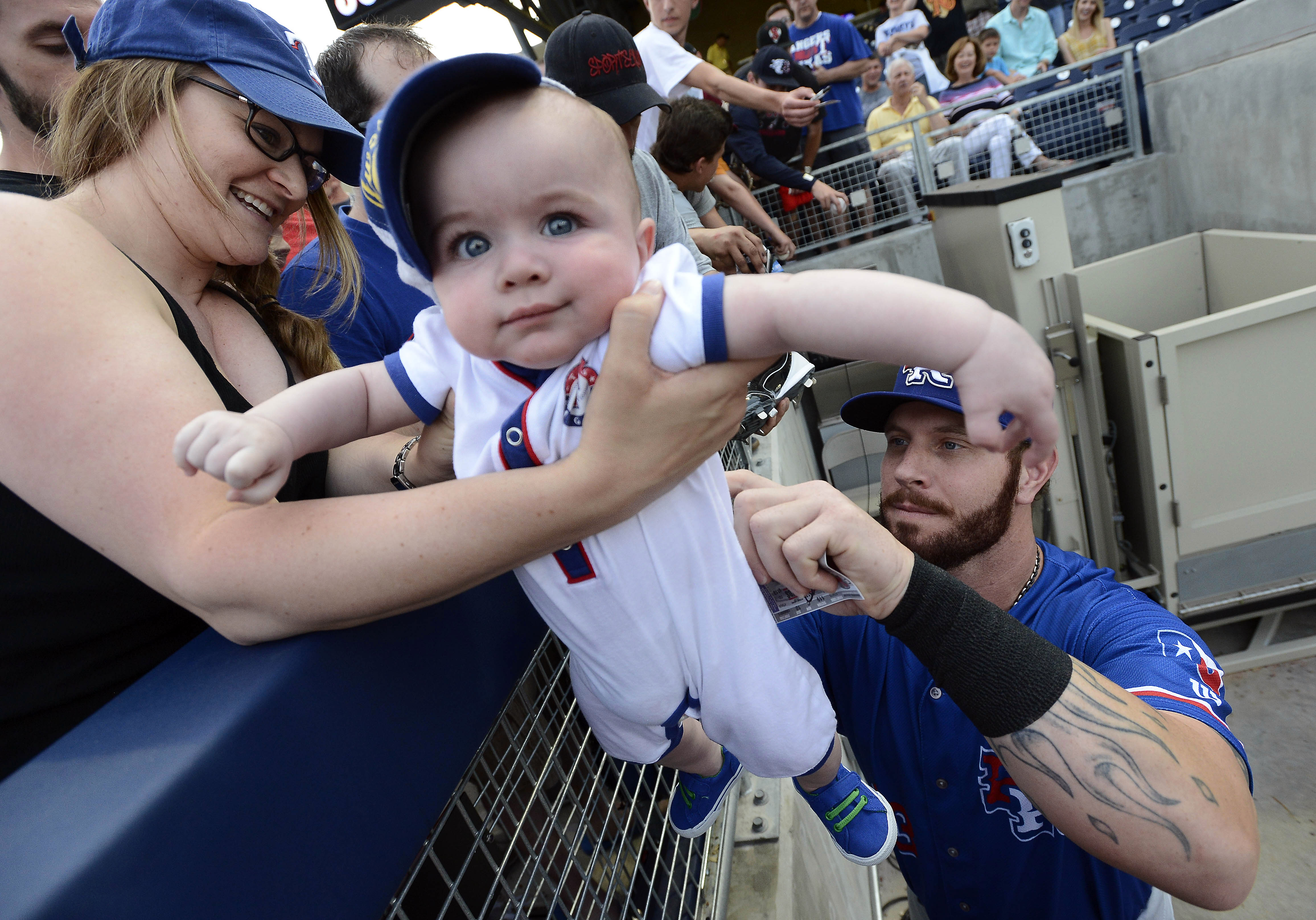 Texas Rangers' Josh Hamilton signs his autograph on the of back 6-month-old Drew Hooker as his mother Melissa holds him before a baseball game against the Nashville Sounds, Monday, May 11, 2015, in Nashville, Tenn. Hamilton is playing for the Round Rock E