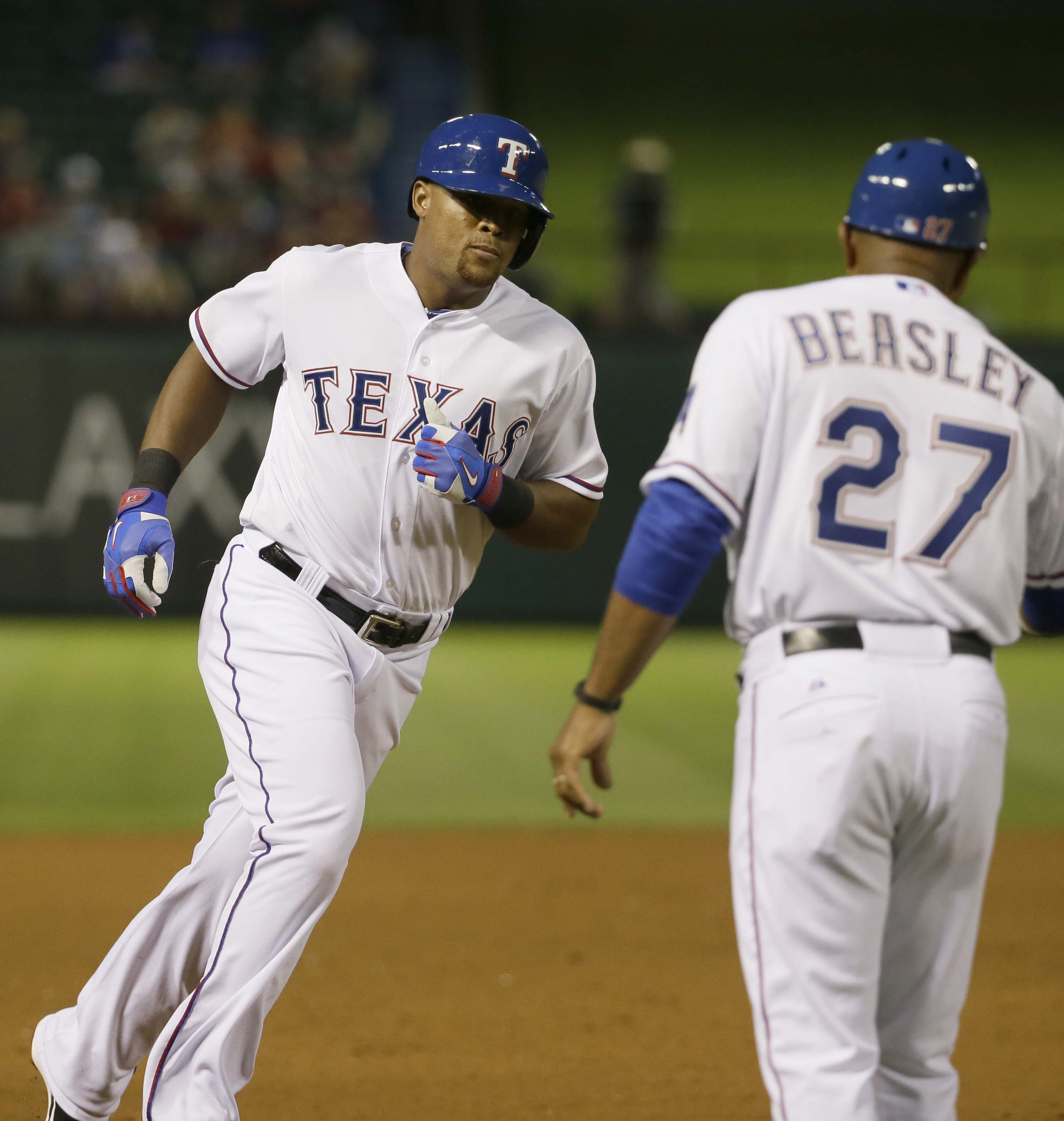 Texas Rangers Adrian Beltre, left, rounds the bases past third base coach Tony Beasley (27) after Beltre's two-run home run during the fourth inning of a baseball game against the Kansas City Royals in Arlington, Texas, Monday, May 11, 2015. Rangers Shin-
