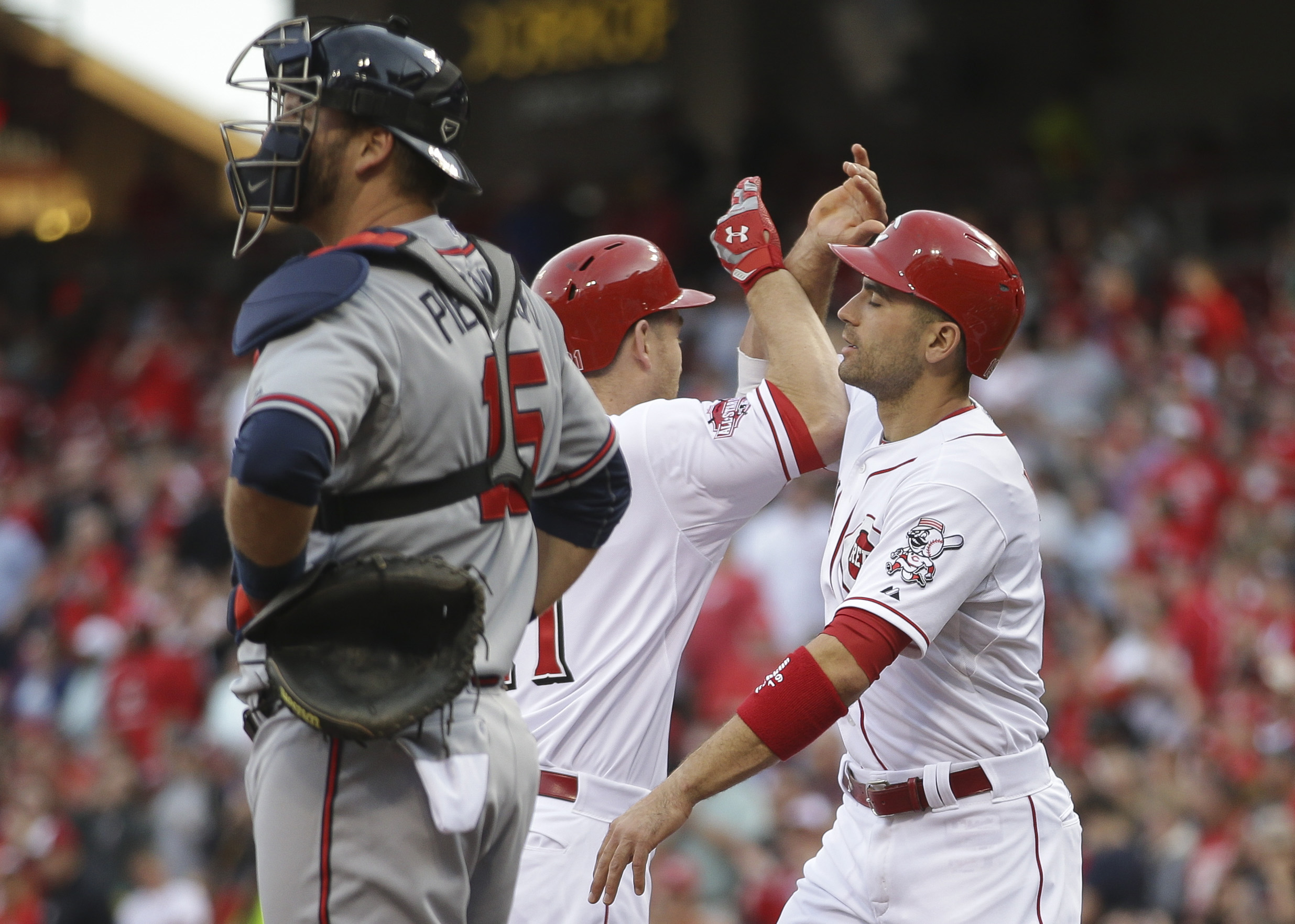 Cincinnati Reds' Todd Frazier, center, celebrates with teammate Joey Votto, right, after hitting a two-run home run as Atlanta Braves catcher A.J. Pierzynski stands at home plate in the first inning of a baseball game, Tuesday, May 12, 2015, in Cincinnati