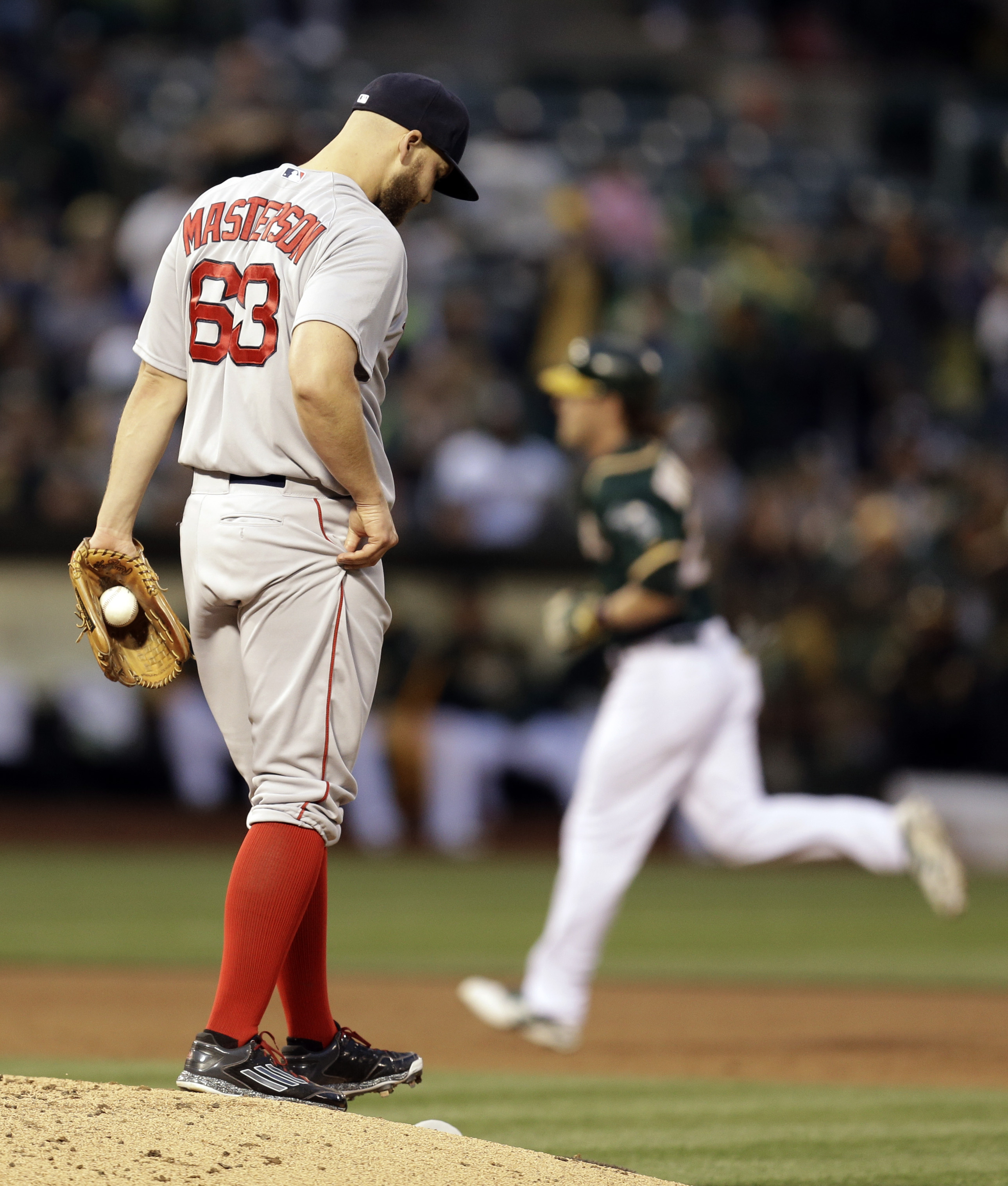 Boston Red Sox pitcher Justin Masterson, left, walks back to the mound after giving up a home run to Oakland Athletics' Josh Reddick, running the bases, right, in the third inning of a baseball game Tuesday, May 12, 2015, in Oakland, Calif. (AP Photo/Ben