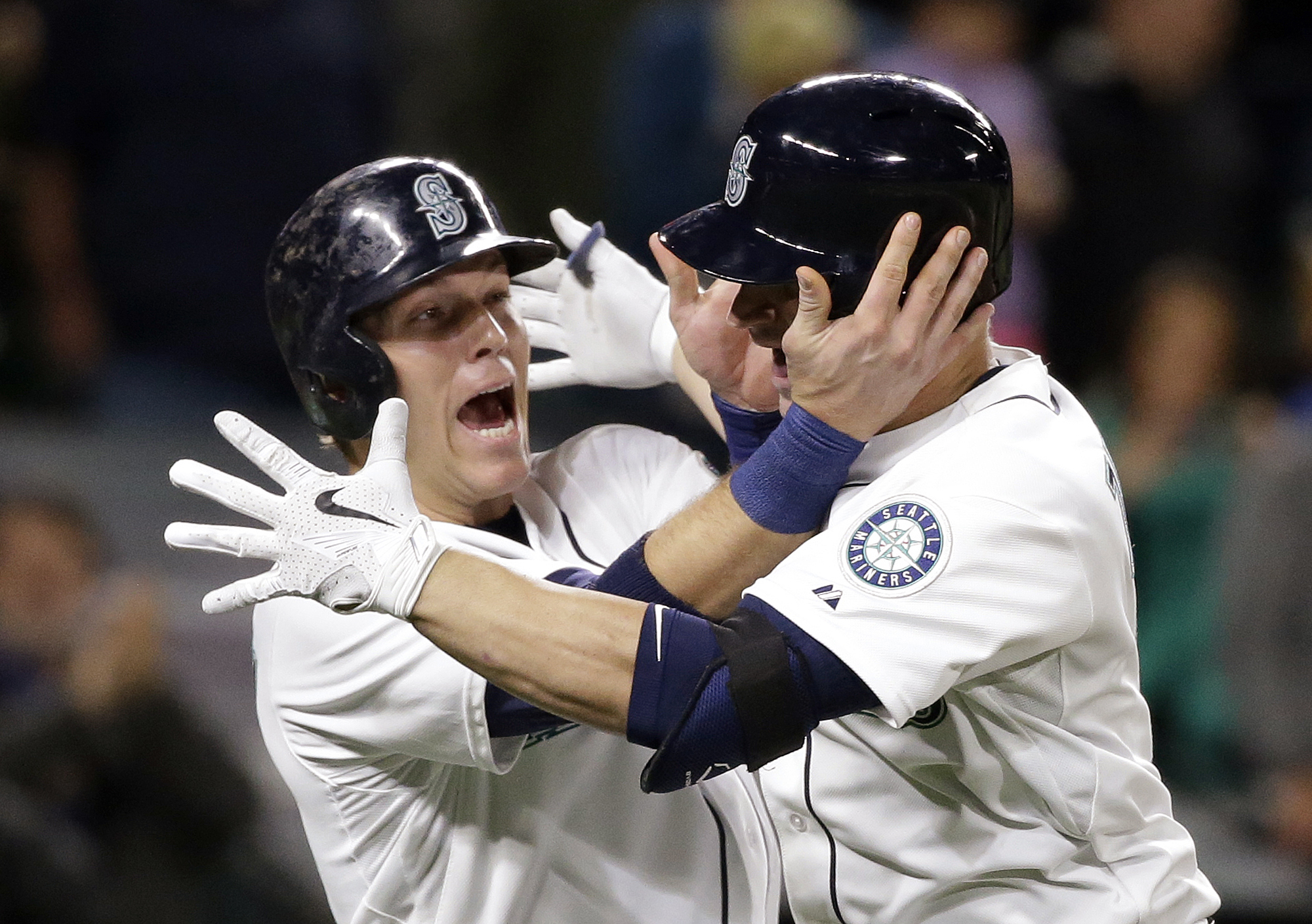 Seattle Mariners' Logan Morrison, left, greets Mike Zunino at home after scoring on Zunino's two-run home run against the San Diego Padres during the seventh inning of a baseball game Tuesday, May 12, 2015, in Seattle. (AP Photo/Elaine Thompson)