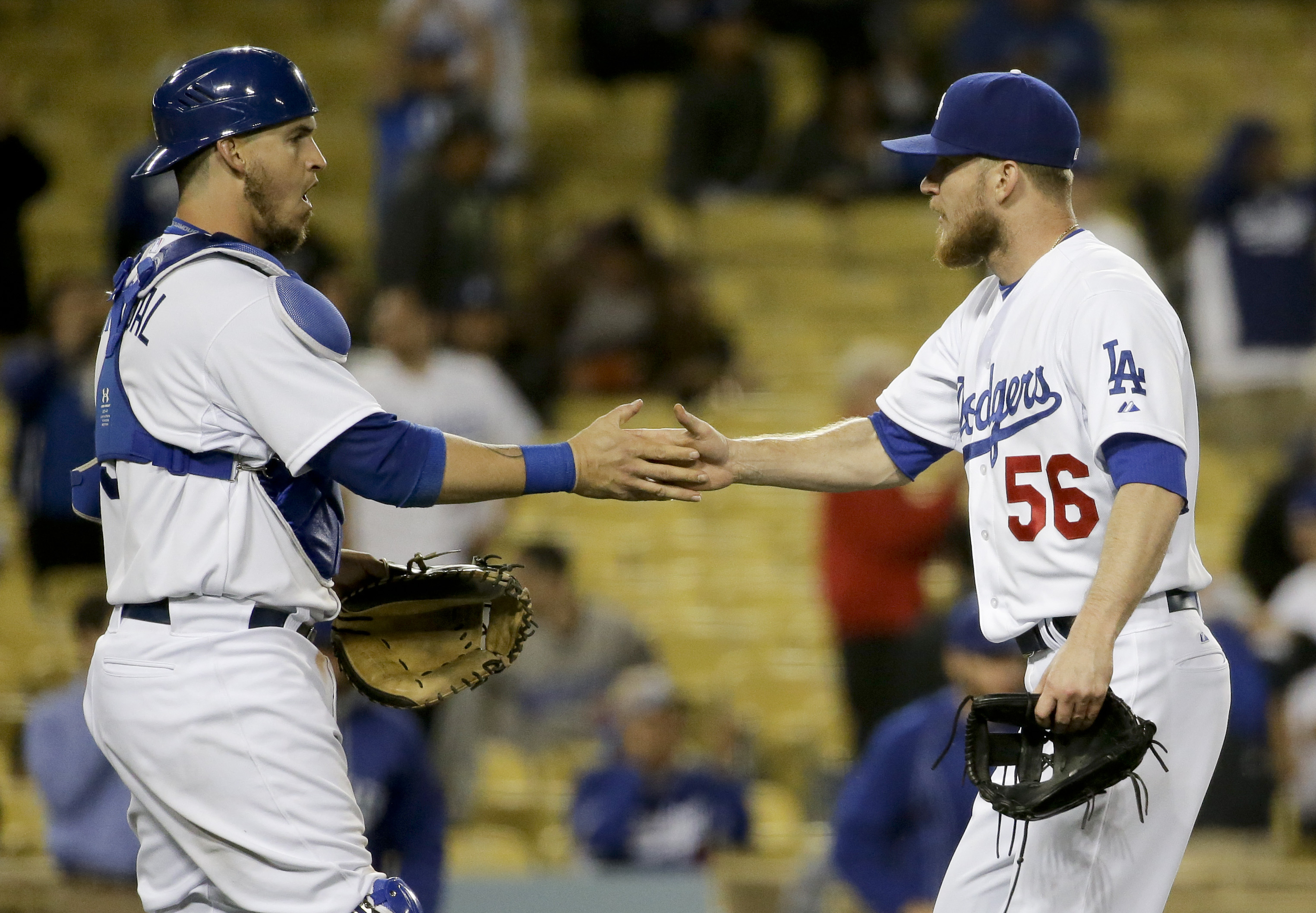 Los Angeles Dodgers catcher Yasmani Grandal, left, and relief pitcher J.P. Howell celebrate after the Dodgers' 11-1 win against the Miami Marlins during a baseball game in Los Angeles, Tuesday, May 12, 2015. (AP Photo/Chris Carlson)