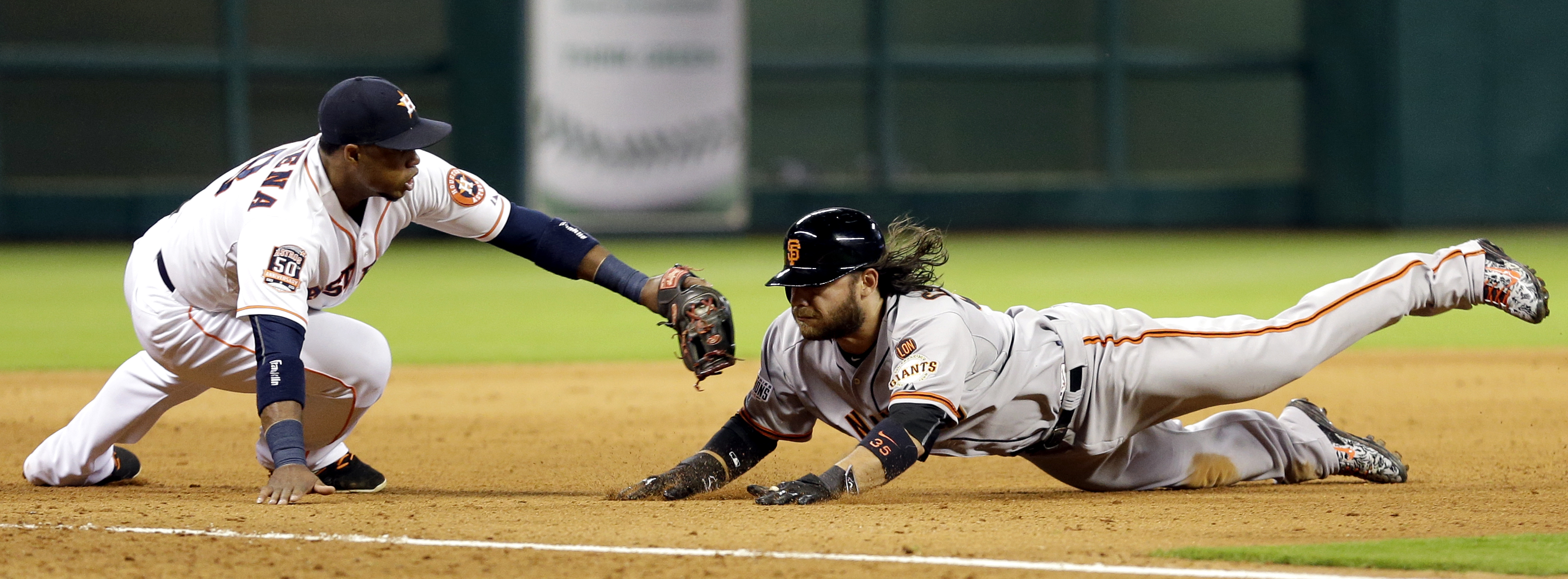 San Francisco Giants' Brandon Crawford, right, is tagged out by Houston Astros third baseman Luis Valbuena, left, while trying to advance from second to third on a ball hit by Nori Aoki during the ninth inning of a baseball game Wednesday, May 13, 2015, i
