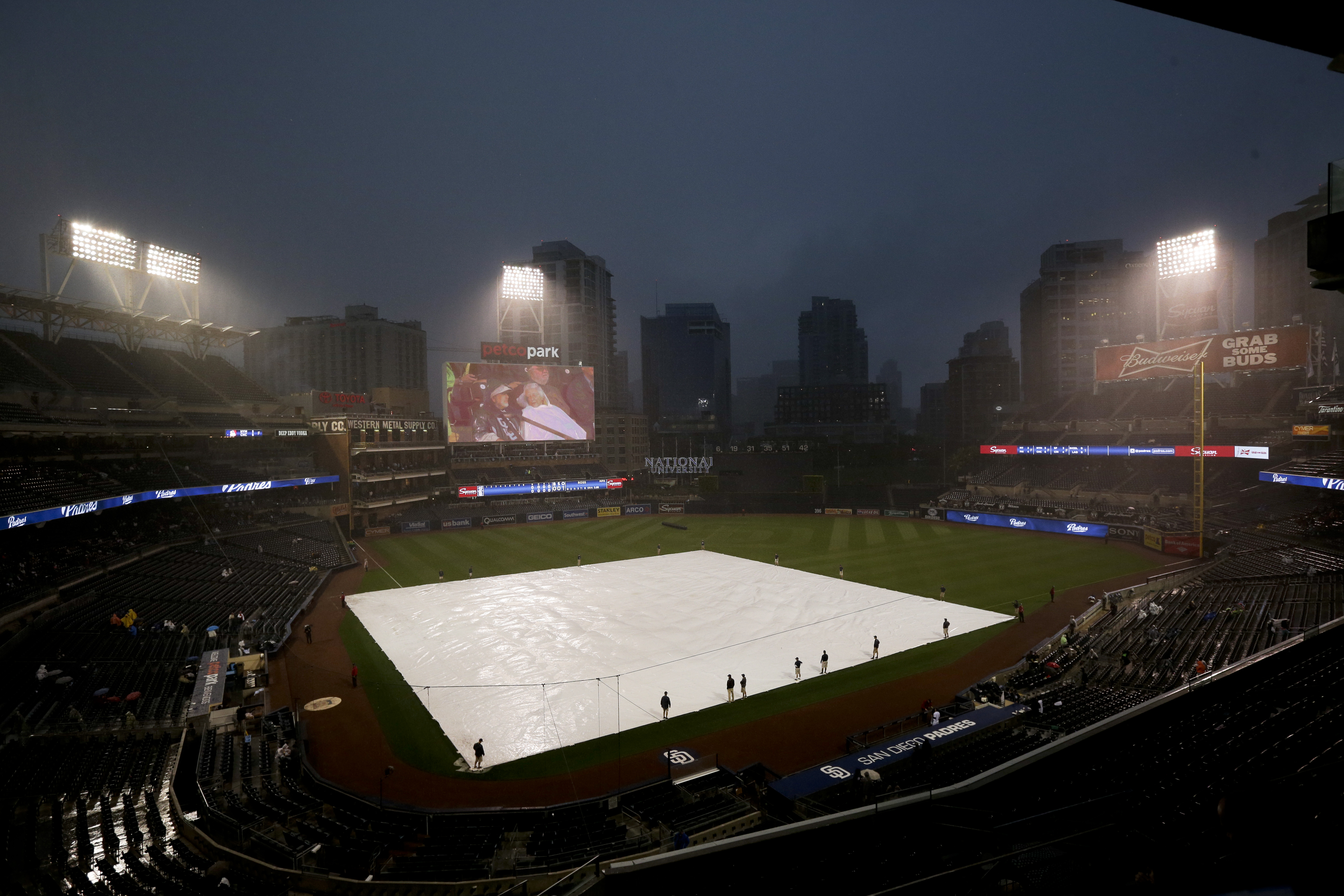 The infield at Petco Park sits covered during a rain delay in a baseball game between the San Diego Padres and the Washington Nationals on Thursday, May 14, 2015, in San Diego. (AP Photo/Gregory Bull)