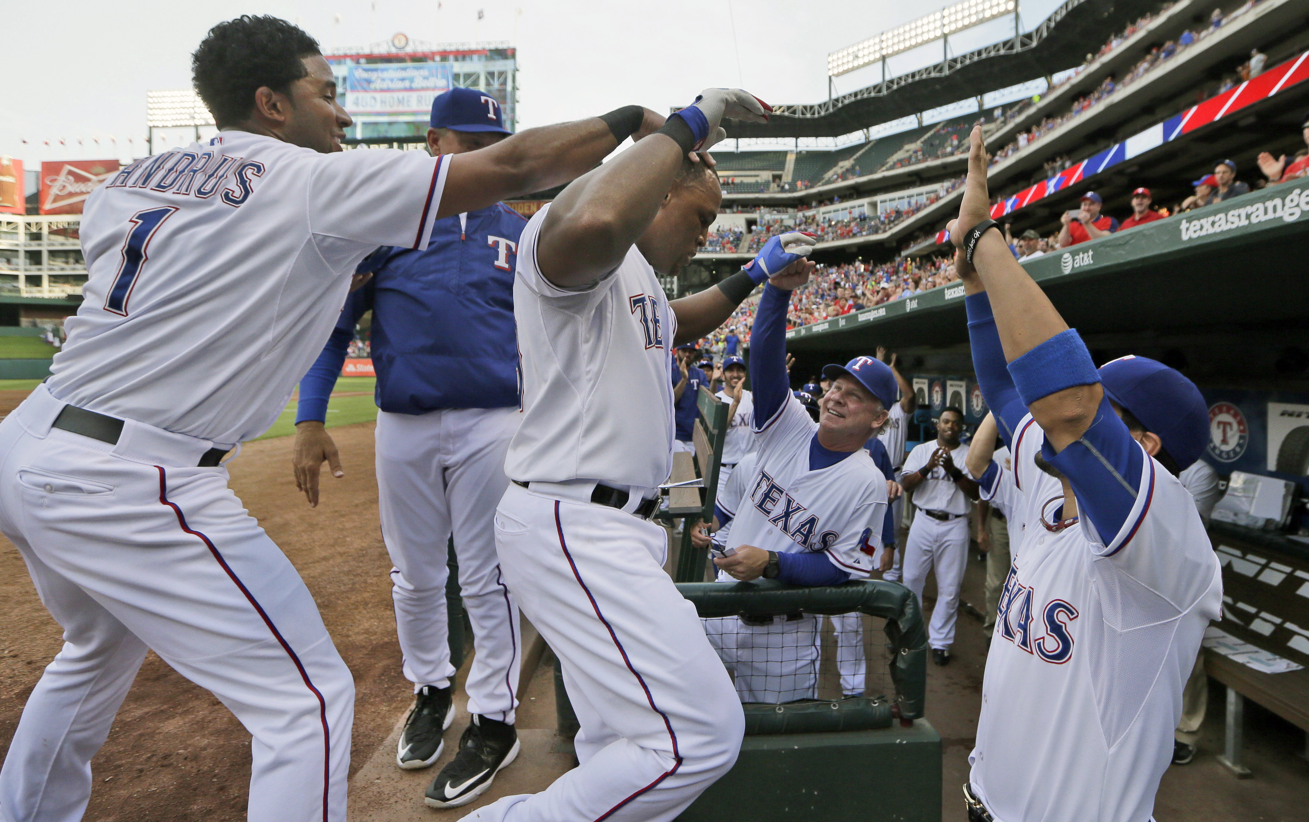 Texas Rangers Adrian Beltre, center left, celebrates his solo home run Elvis Andrus (1), Robinson Chirinos, right, and bench coach Steve Buechele during the first inning of a baseball game against the Cleveland Indians in Arlington, Texas, Friday, May 15,