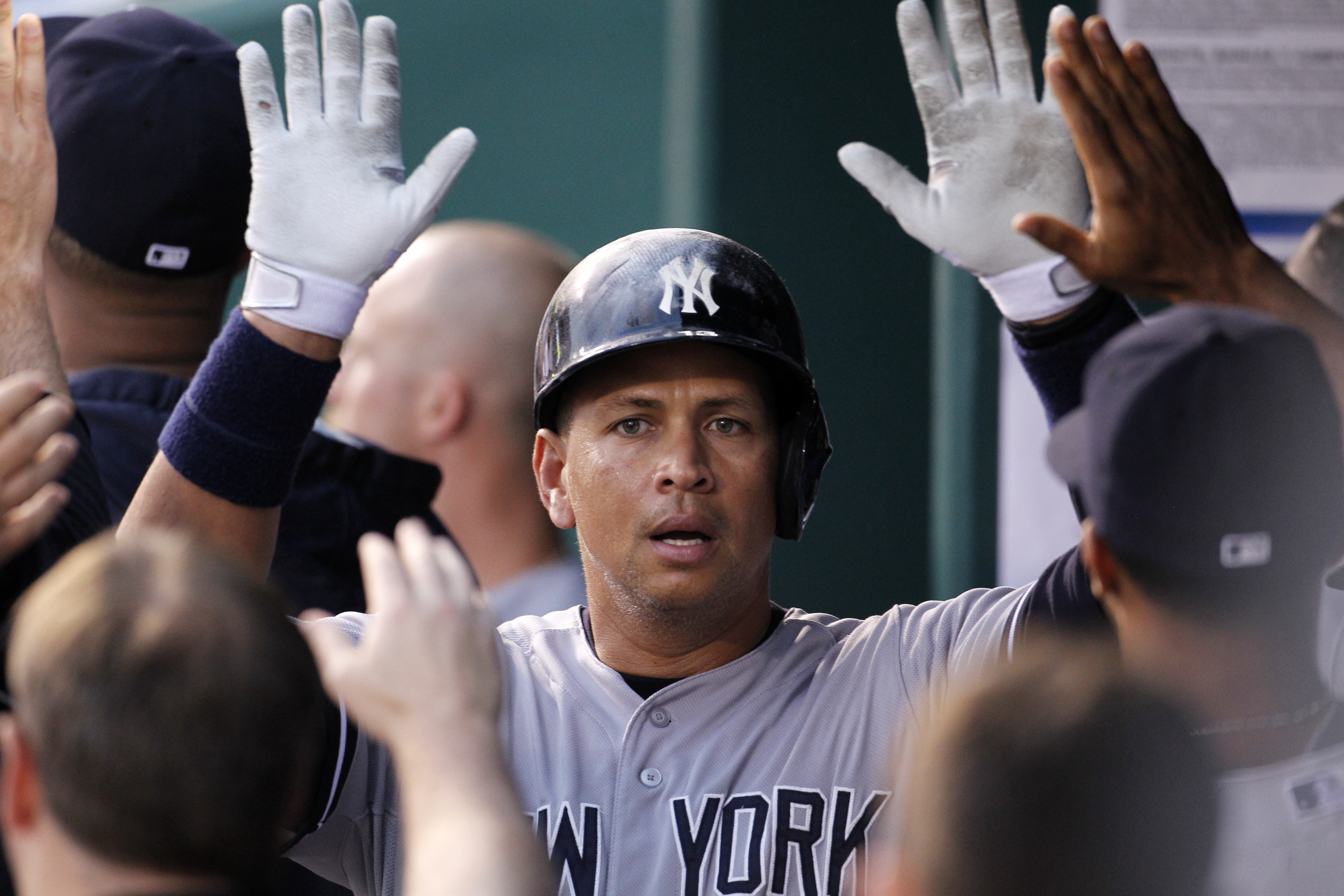 New York Yankees' Alex Rodriguez is congratulated in the dugout after scoring from third base in the fourth inning of a baseball game against the Kansas City Royals at Kauffman Stadium in Kansas City, Mo., Friday, May 15, 2015. Rodriguez scored on a sacri