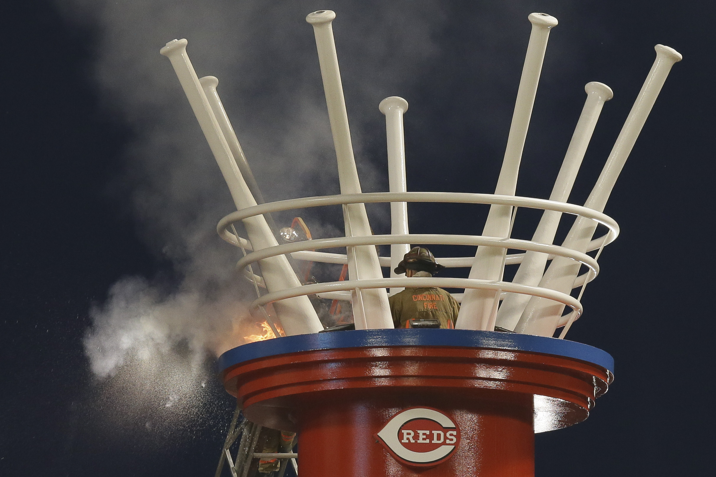 A firefighter hoses down a blaze in one of the outfield stacks at Great American Ballpark in the sixth inning of a baseball game between the San Francisco Giants and the Cincinnati Reds, Friday, May 15, 2015, in Cincinnati. (AP Photo/John Minchillo)