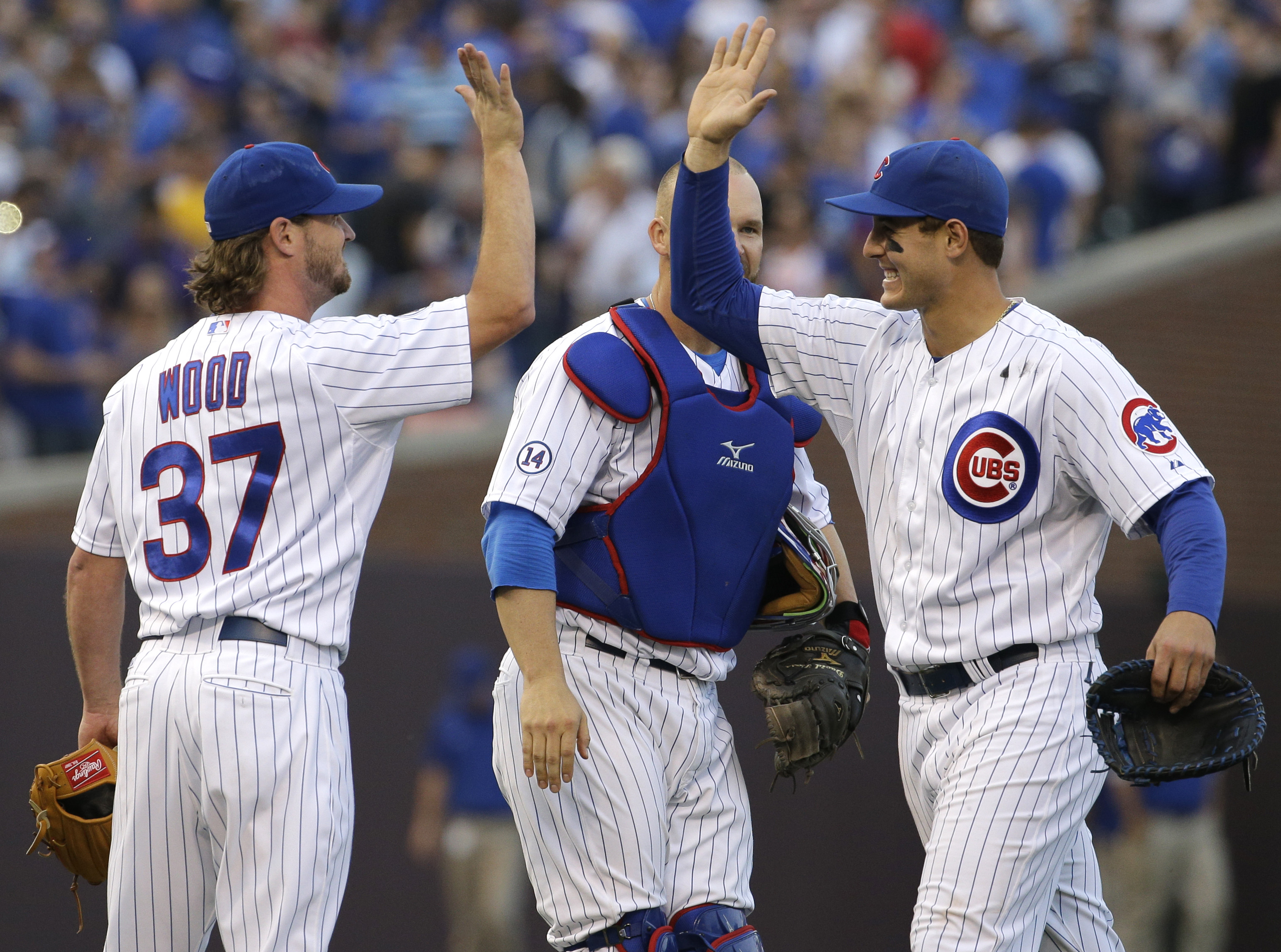 Chicago Cubs first baseman Anthony Rizzo, right, celebrates with closer Travis Wood, left, and catcher David Ross after they defeated the Pittsburgh Pirates 4-1 in a baseball game Saturday, May 16, 2015, in Chicago. (AP Photo/Nam Y. Huh)