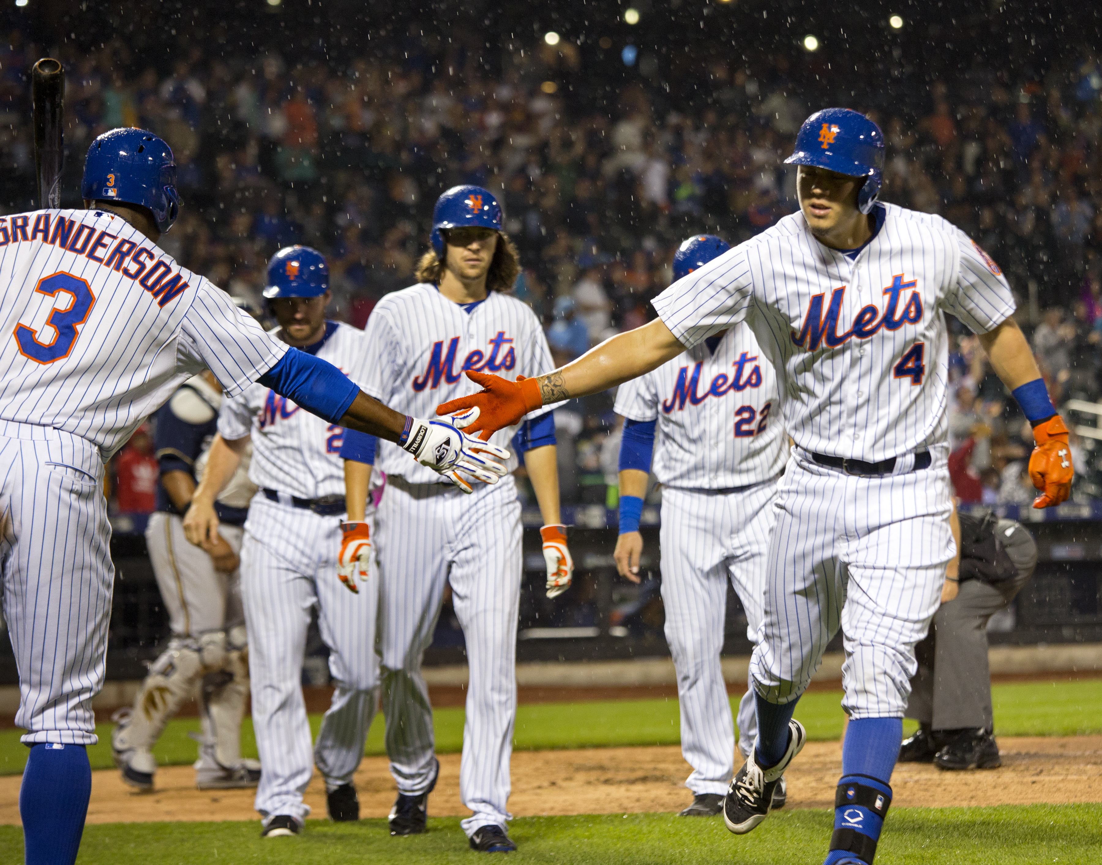 New York Mets' Wilmer Flores (4) is congratulated by teammate Curtis Granderson after hitting a grand slam against the Milwaukee Brewers in the fourth inning of a baseball game Saturday, May 16, 2015, in New York. (AP Photo/Craig Ruttle)