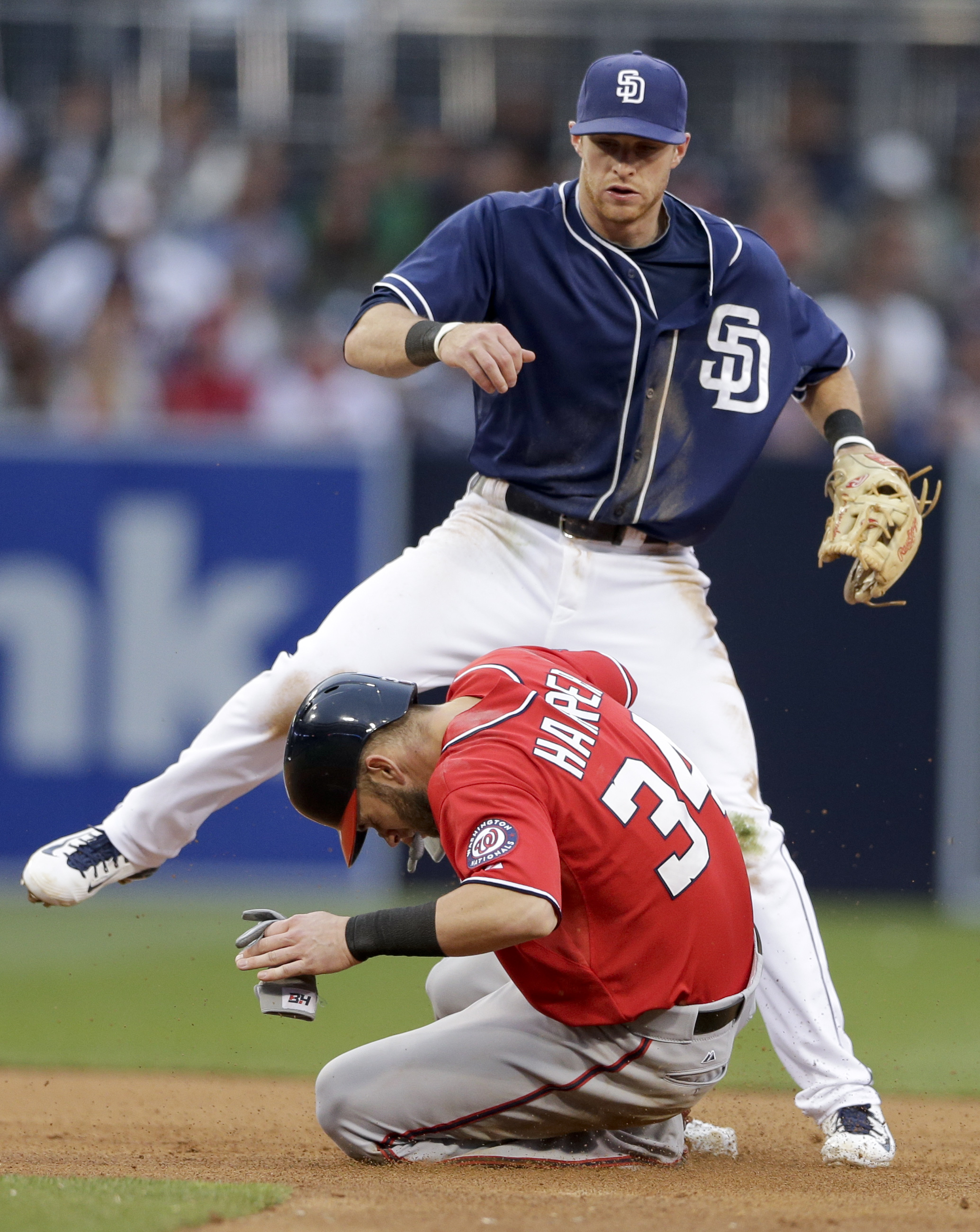 Washington Nationals' Bryce Harper, below, collides with San Diego Padres second baseman Cory Spangenberg, above, as he watches his throw to complete a double play during the fifth inning in a baseball game Saturday, May 16, 2015, in San Diego. (AP Photo/