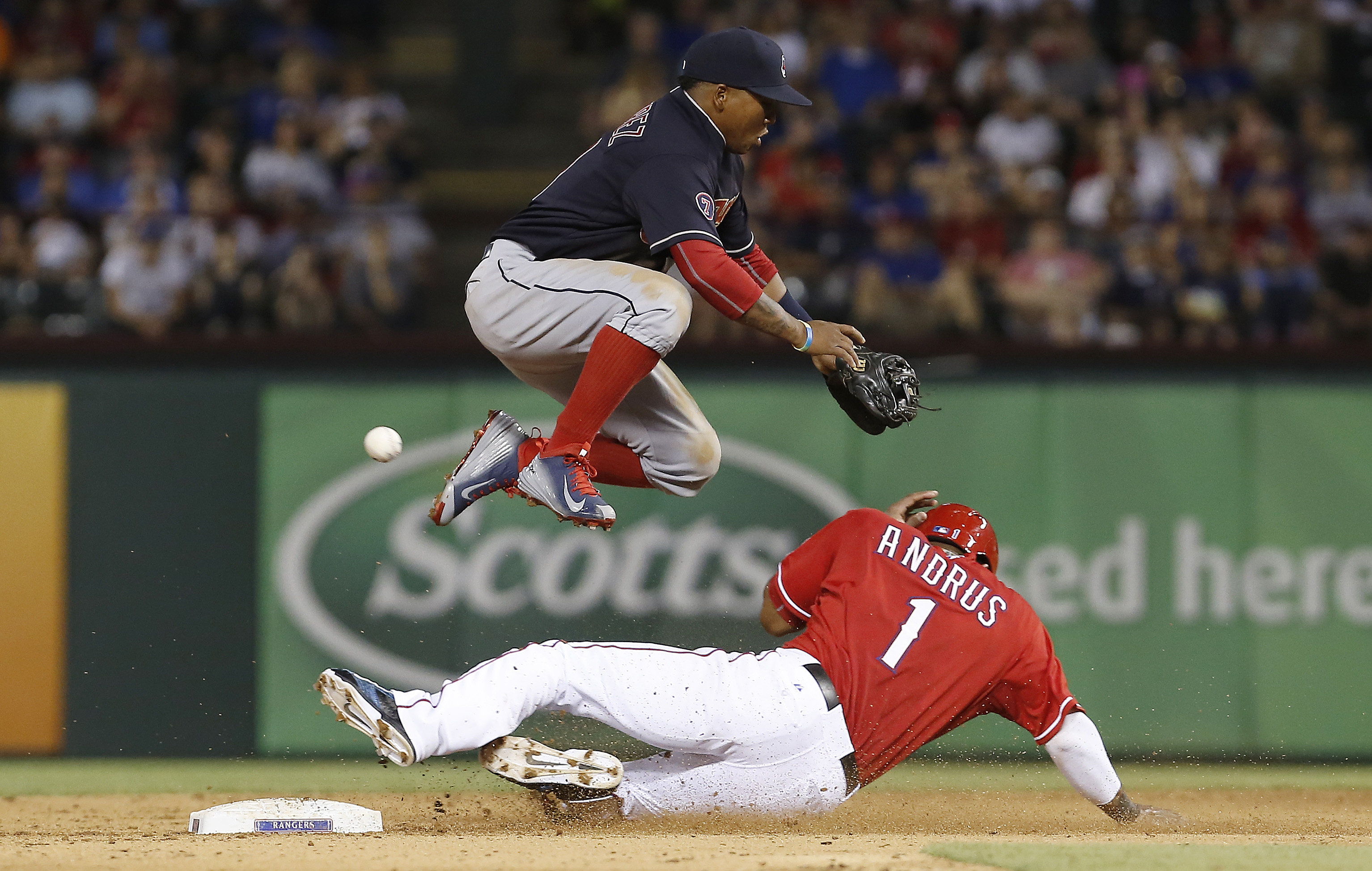 Cleveland Indians shortstop Jose Ramirez, top, is unable to catch the throw from catcher Roberto Perez as Texas Rangers' Elvis Andrus (1) steals second base during the fifth inning of a baseball game, Saturday, May 16, 2015, in Arlington, Texas. The throw