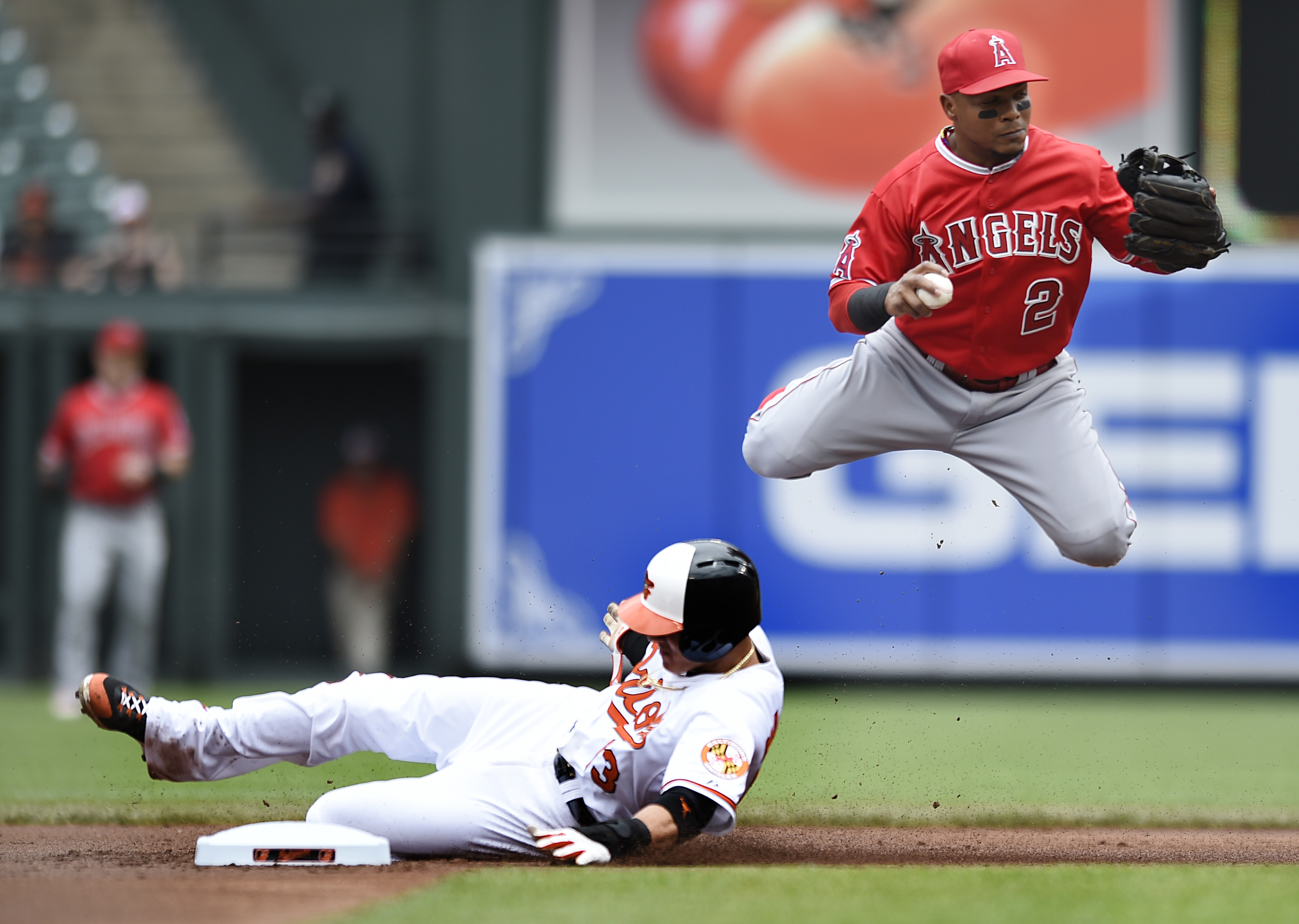Baltimore Orioles' Manny Machado, bottom, is out at second on a force as Los Angeles Angels shortstop Erick Aybar jumps over him in the first inning of a baseball game Sunday, May 17, 2015, in Baltimore. (AP Photo/Gail Burton)