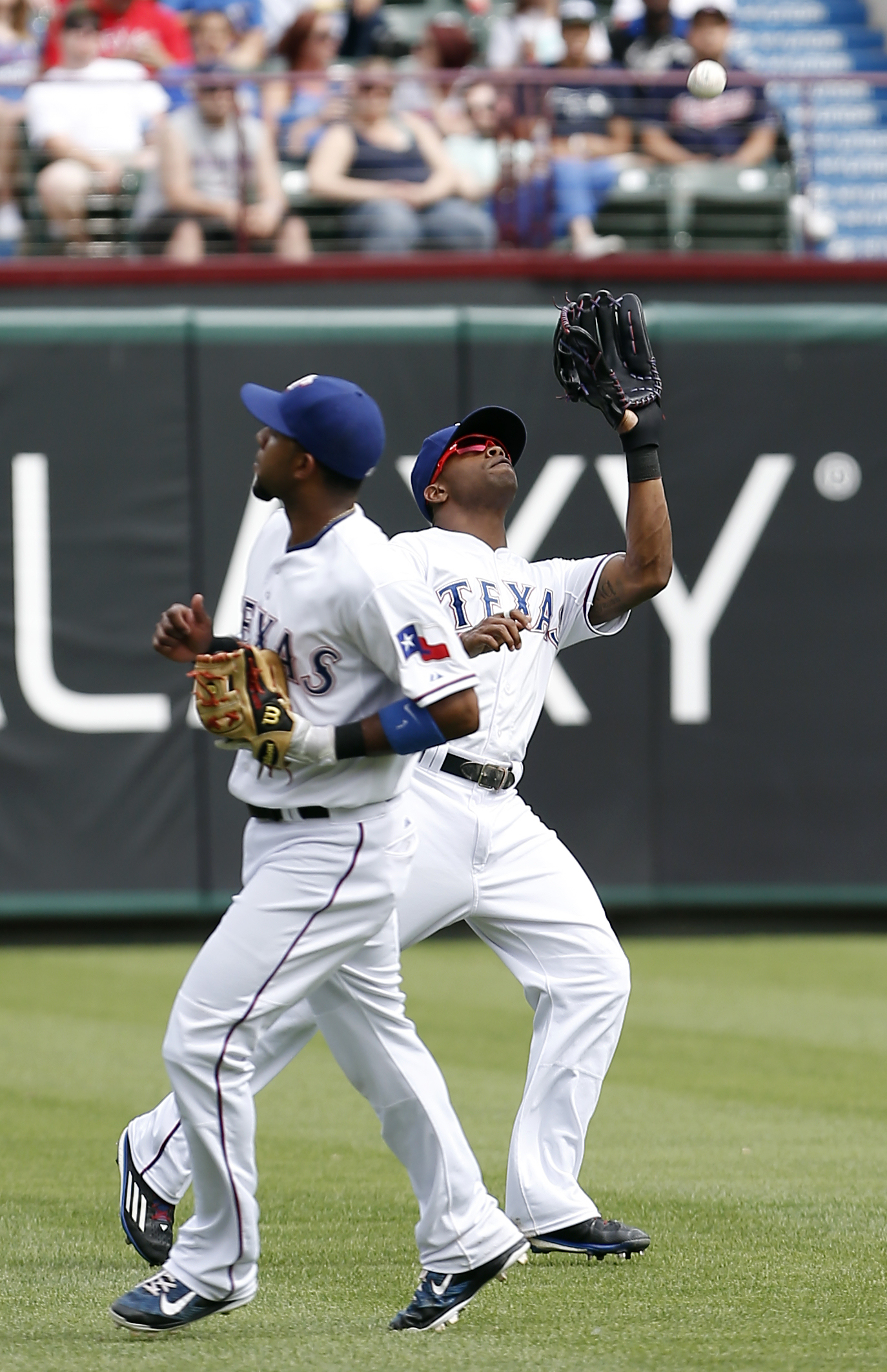 Texas Rangers shortstop Elvis Andrus, left, looks on as left fielder Delino DeShields, right, catches a fly-out hit by Cleveland Indians' Jason Kipnis during the sixth inning of a baseball game, Sunday, May 17, 2015, in Arlington, Texas. (AP Photo/Brandon