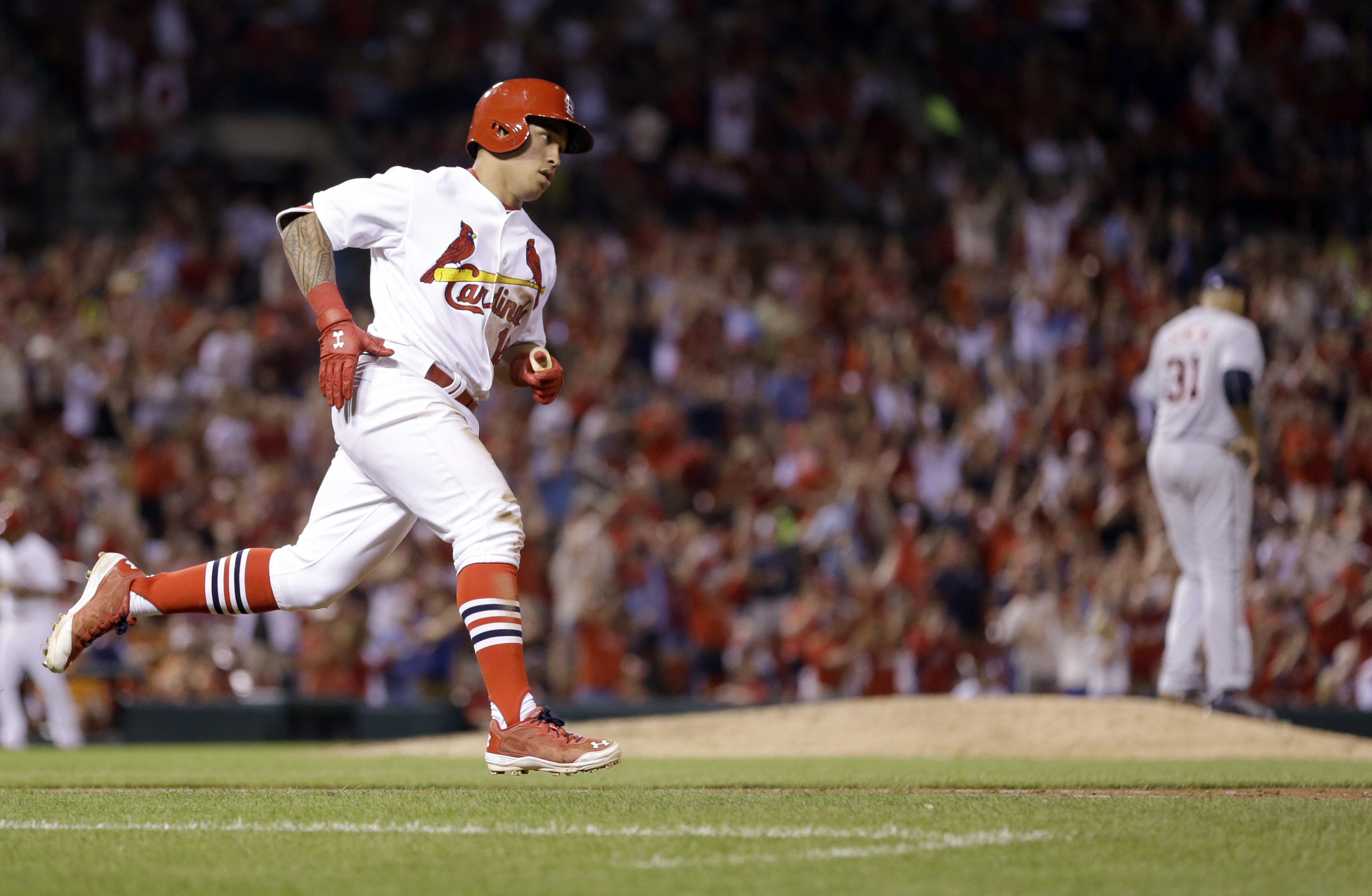 St. Louis Cardinals' Kolten Wong, left, rounds the bases after hitting a solo home run off Detroit Tigers starting pitcher Alfredo Simon, right, during the sixth inning of a baseball game Sunday, May 17, 2015, in St. Louis. (AP Photo/Jeff Roberson)