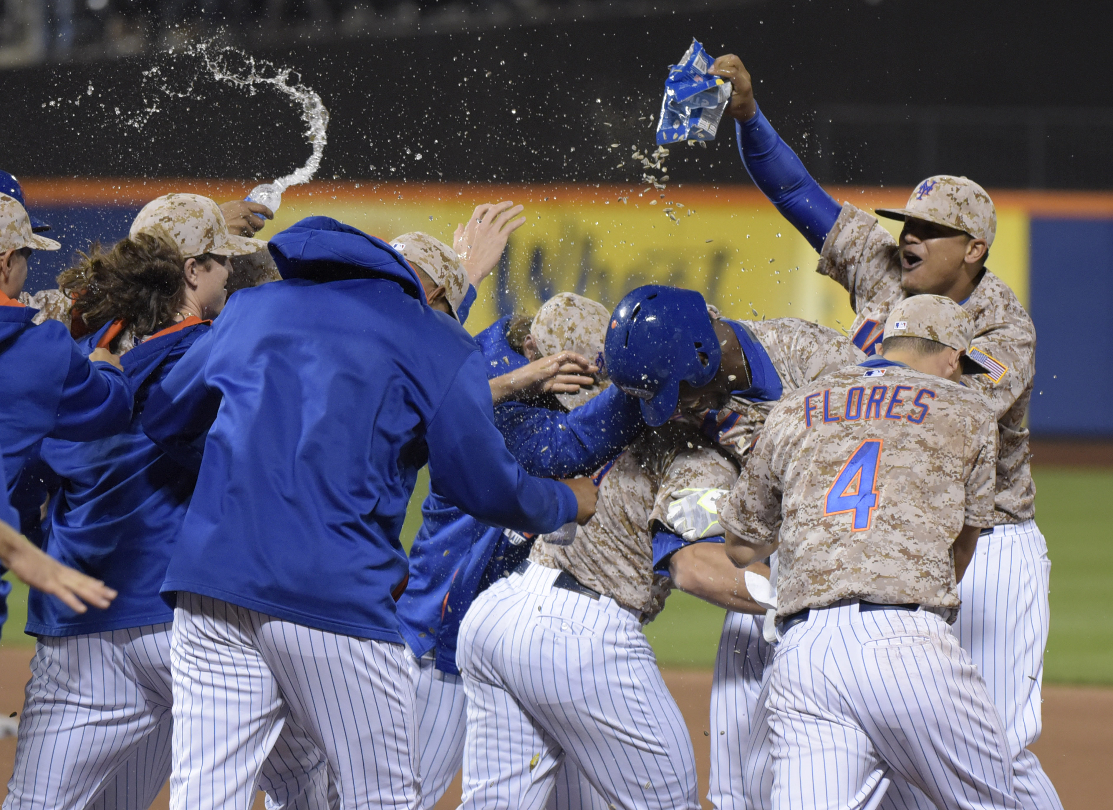 The New York Mets celebrate with John Mayberry Jr. after Mayberry hit an infield single to drive in the winning run as the Mets defeated the St. Louis Cardinals, 2-1, in the 14th inning of a baseball game Monday, May 18, 2015, at Citi Field in New York. (